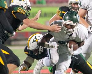 Trinity running back Jovan Smith avoids the outstretched arms of St.Xavier's defensive lineman Andrew Uhls. 30 September 2016