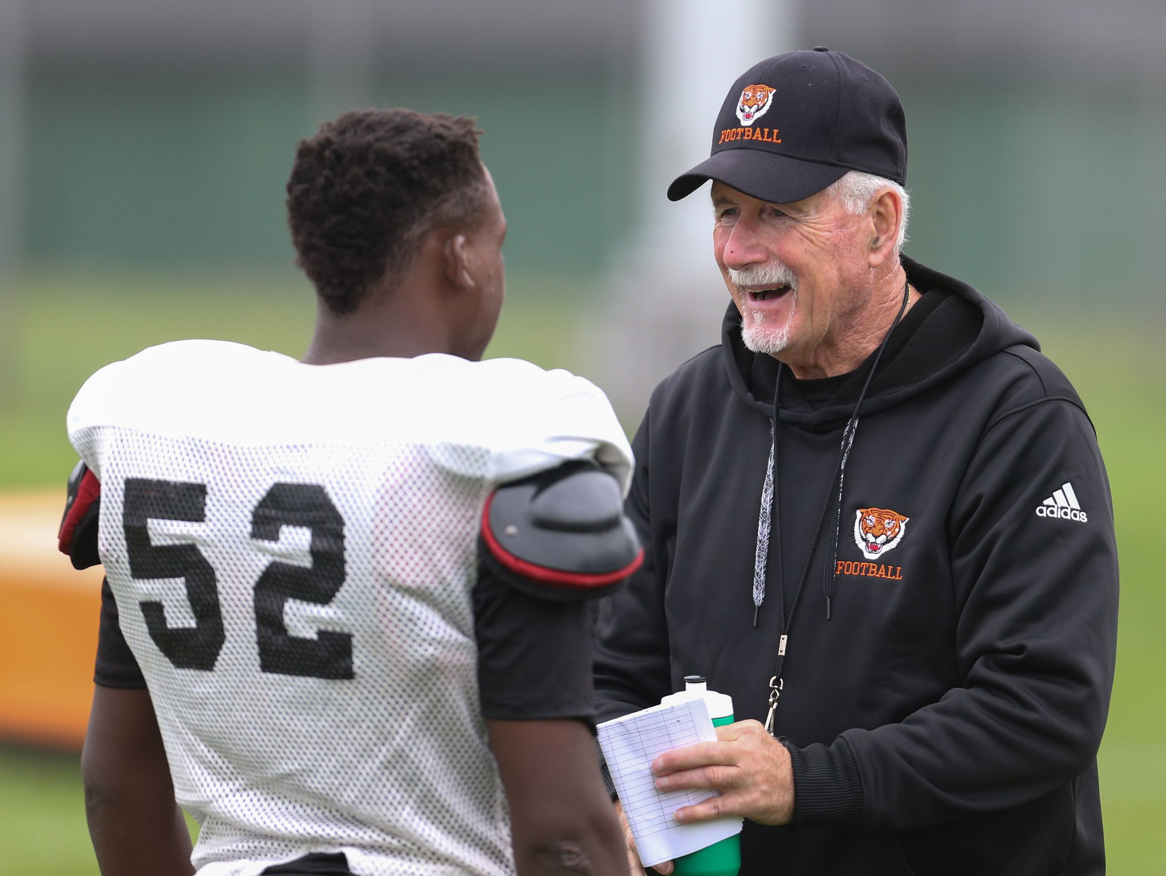 Benton Harbor head football coach Elliot Uzelac talks with Mikel Seals-Porter during practice.
