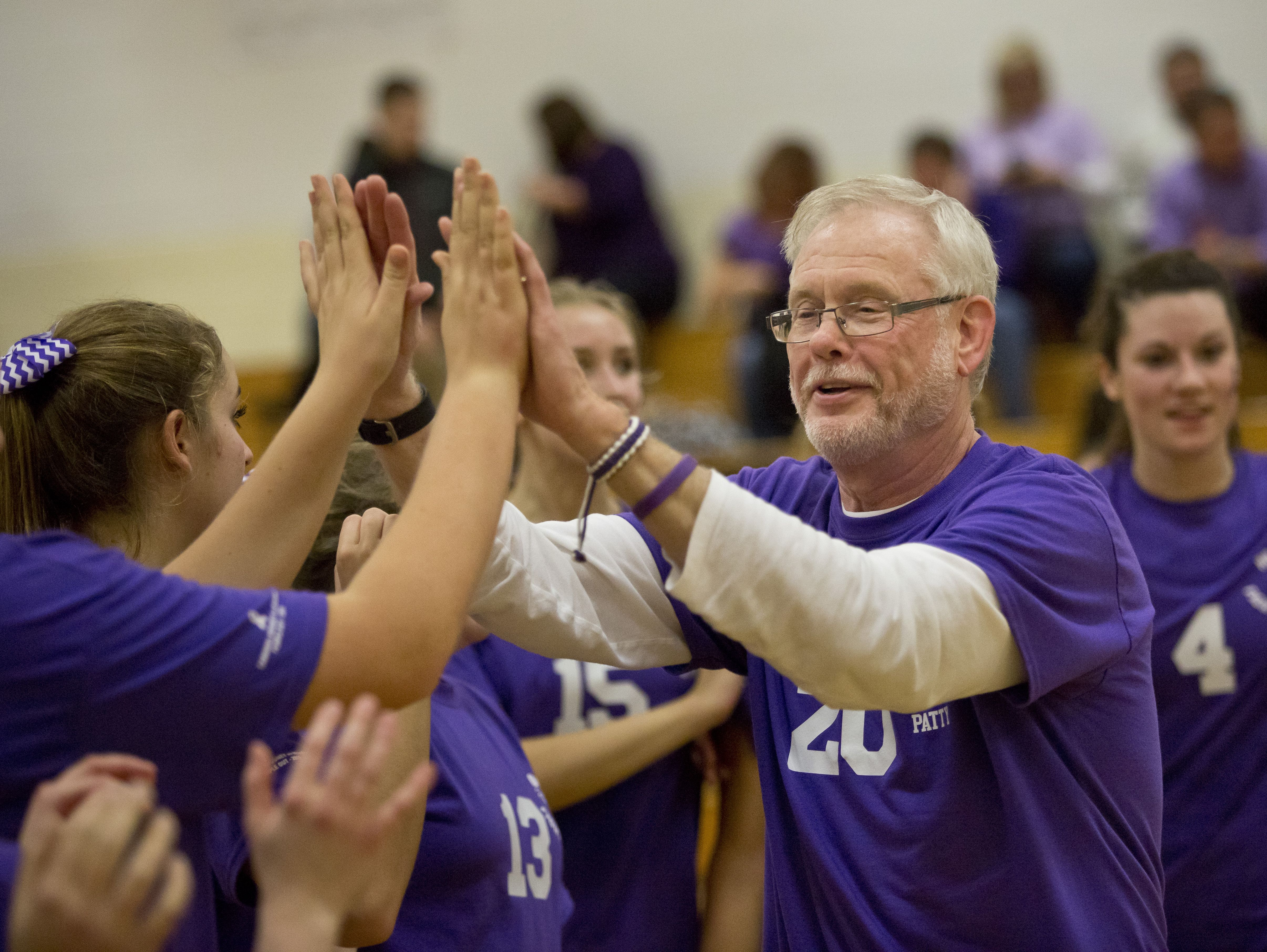 Cardinal Mooney coach Dennis Caulfield claps hands with players after they beat Regina in a volleyball game Wednesday, October 28, 2015 at Cardinal Mooney High School.
