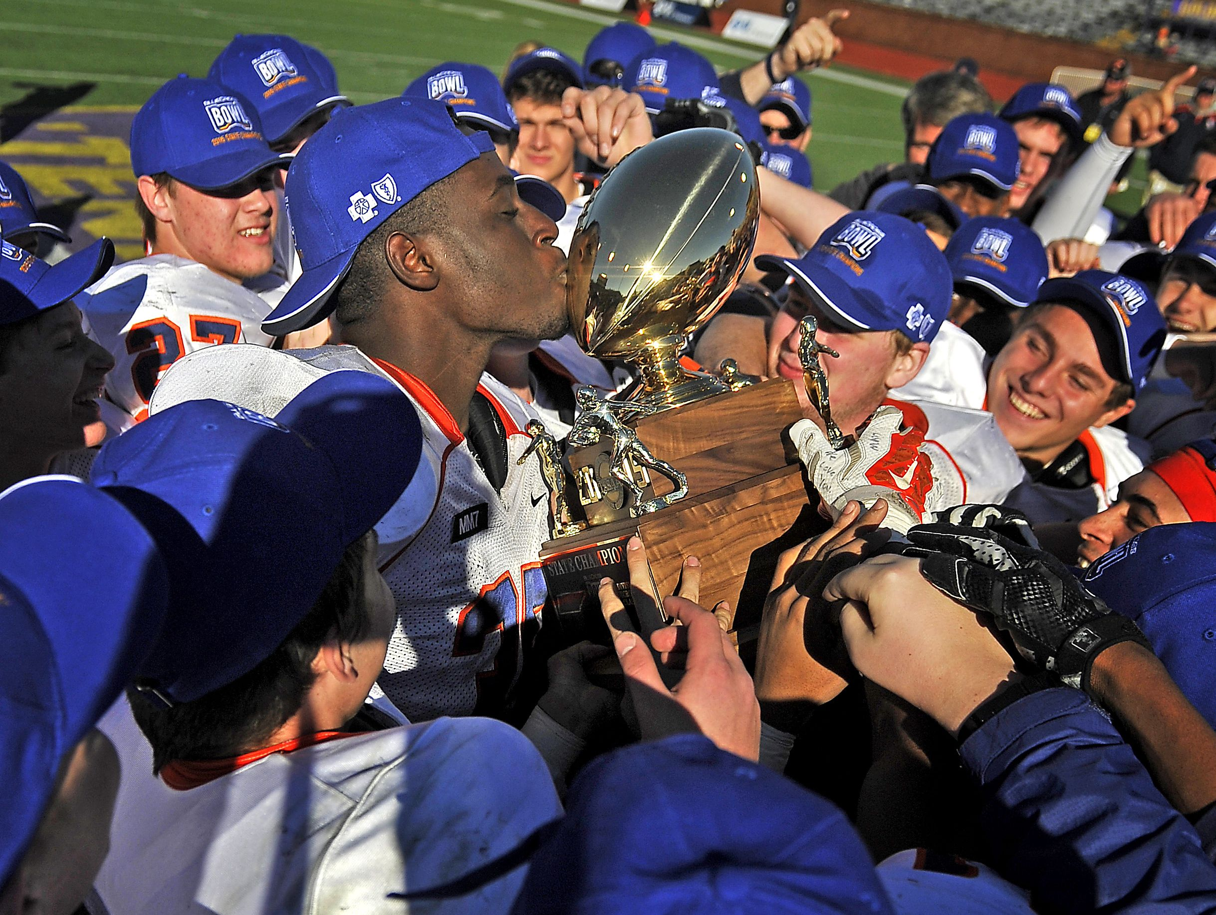 Daniel Bituli (35) kisses the trophy after Nashville Christian beat Greenback 42-14 in the 1A title game, giving the school its first team championship of any kind.