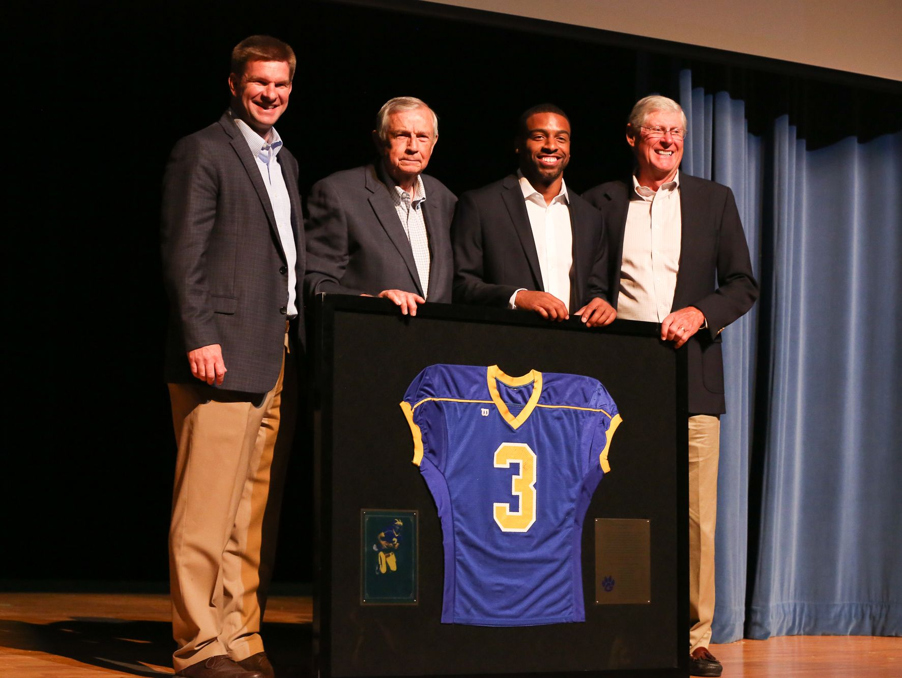 """From left, Goodpasture Principal Lindsey Judd, Goodpasture athletics director Clint Parnell, honoree Keenan Reynolds and former Goodpasture coach David Martin pose with Reynolds' retired high school jersey at the """"Salute to Keenan Reynolds"""" on Friday night at Goodpasture."""