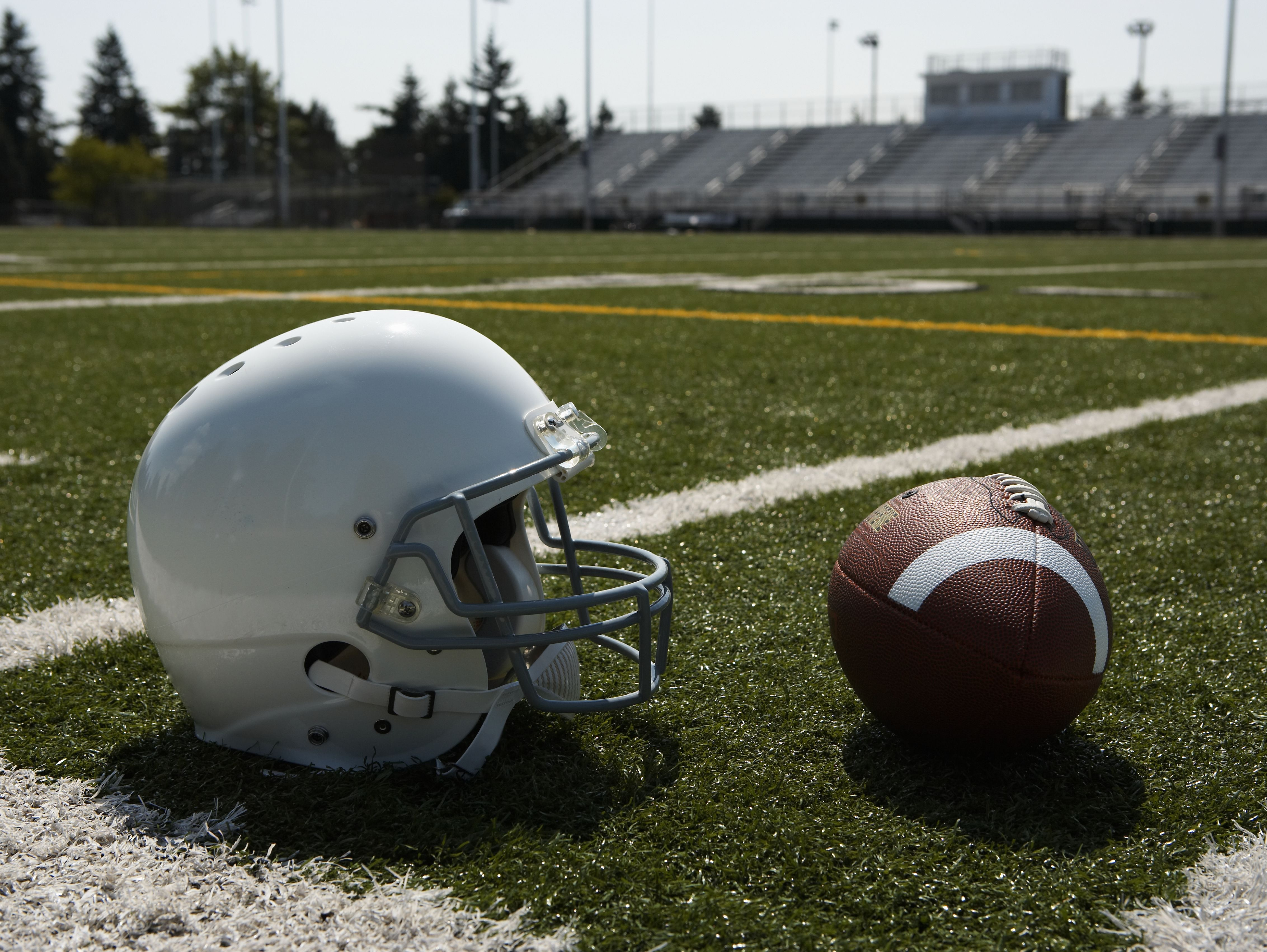 Football and football helmet on football field.