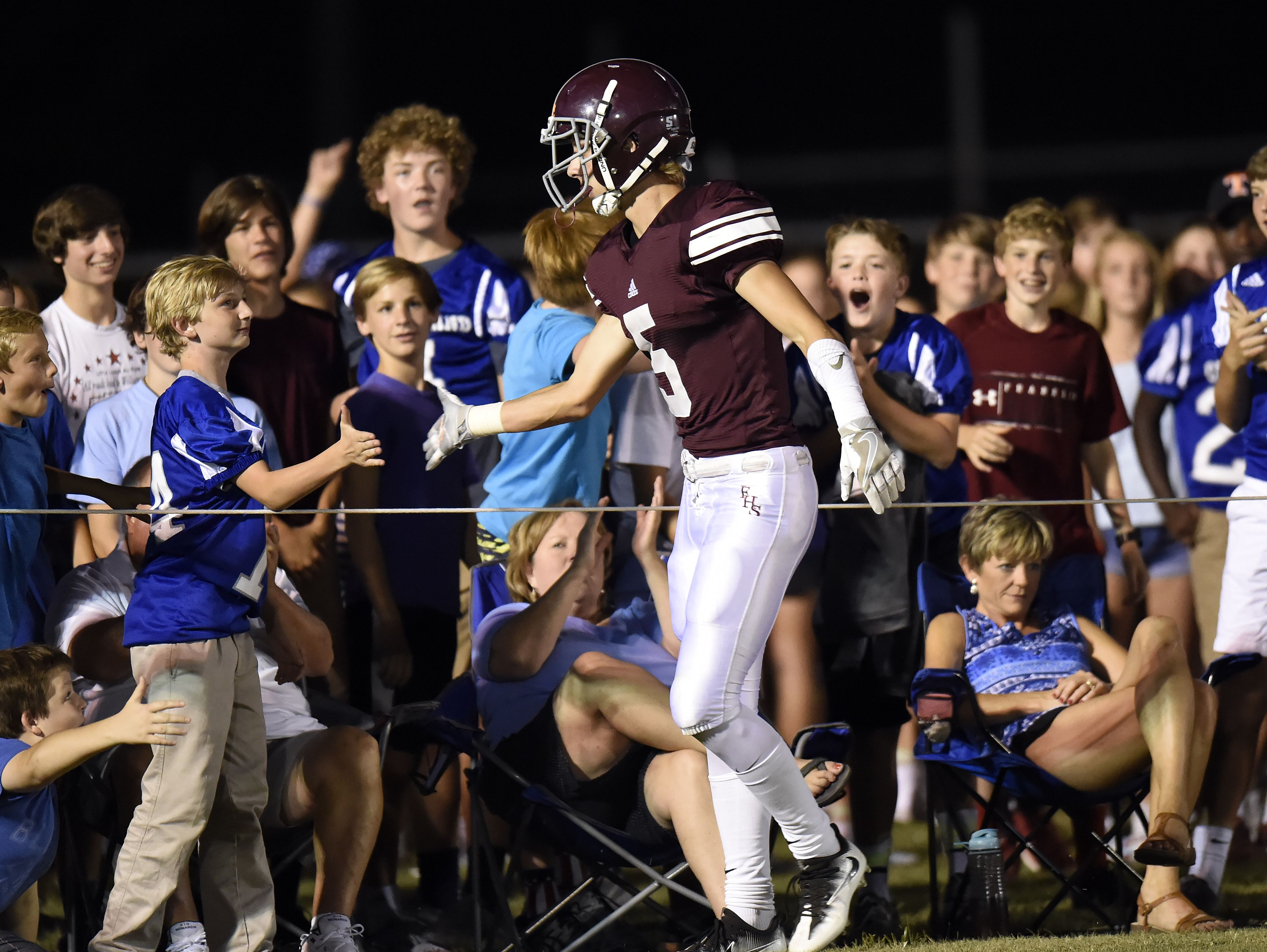 Franklin wide receiver Alex Gaca celebrates with fans after catching a pass for a touchdown during the first half against Brentwood.