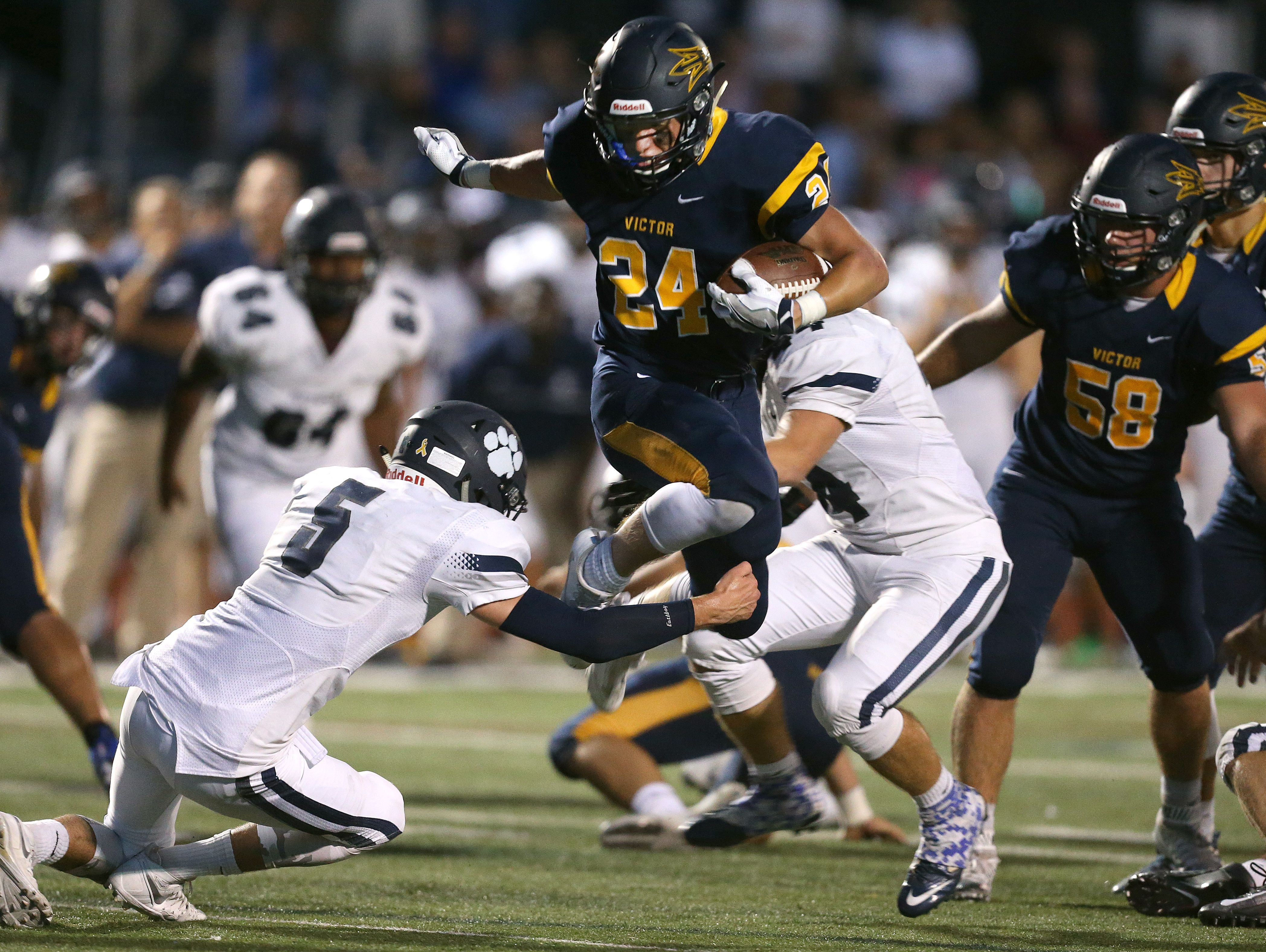 Victor running back Mitchell Spindler (24) leaps over Pittsford's Frankie Imburgia (5) in Week 3. Next for the Blue Devils is Fairport, another undefeated opponent Victor faces at home.