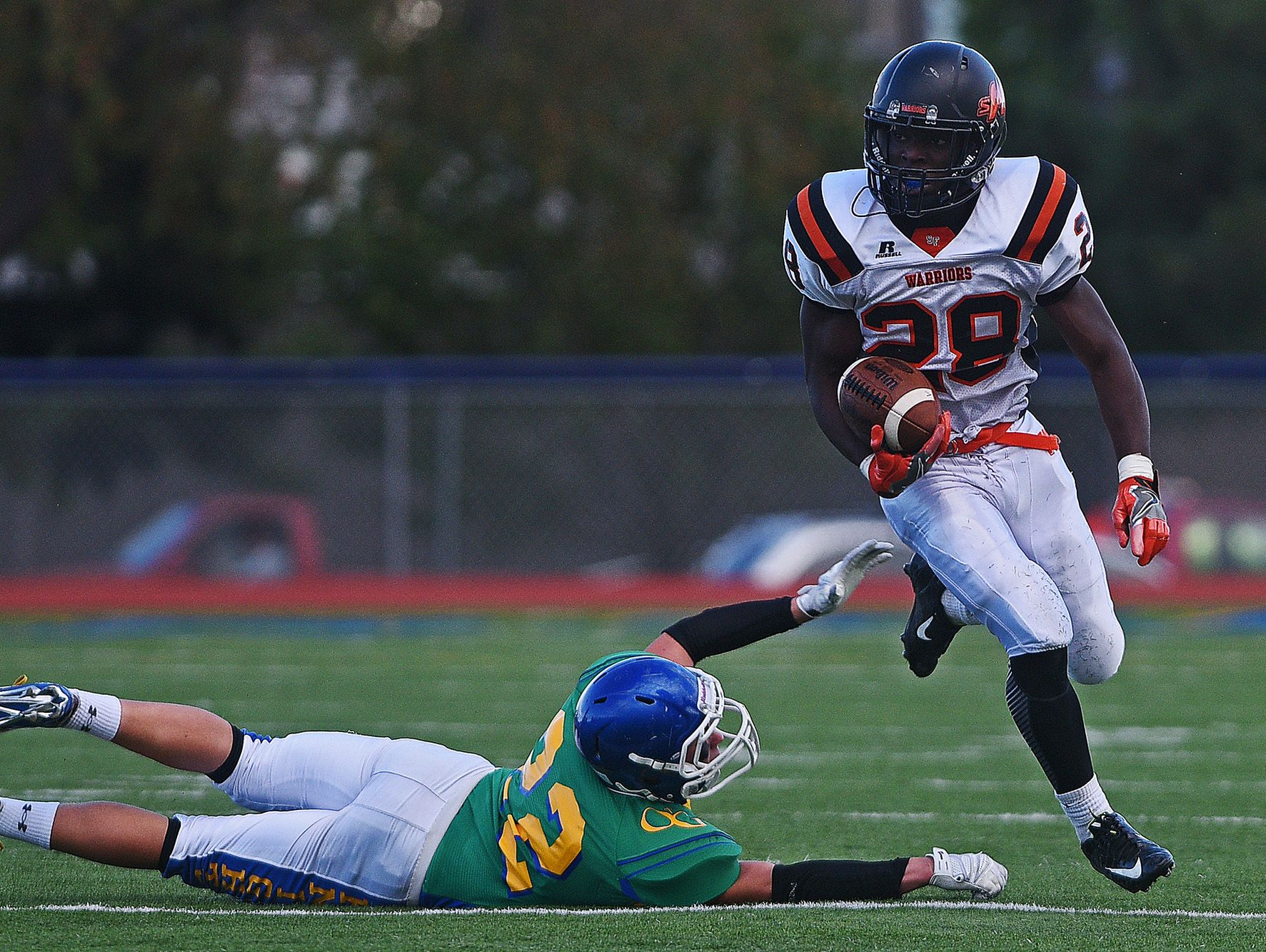 Washington's Tupac Kpeayeh (28) carries the ball past O'Gorman's Dylan Kallhoff (22) during a game Friday, Sept. 16, 2016, at McEneaney Field on the O'Gorman High School campus in Sioux Falls.