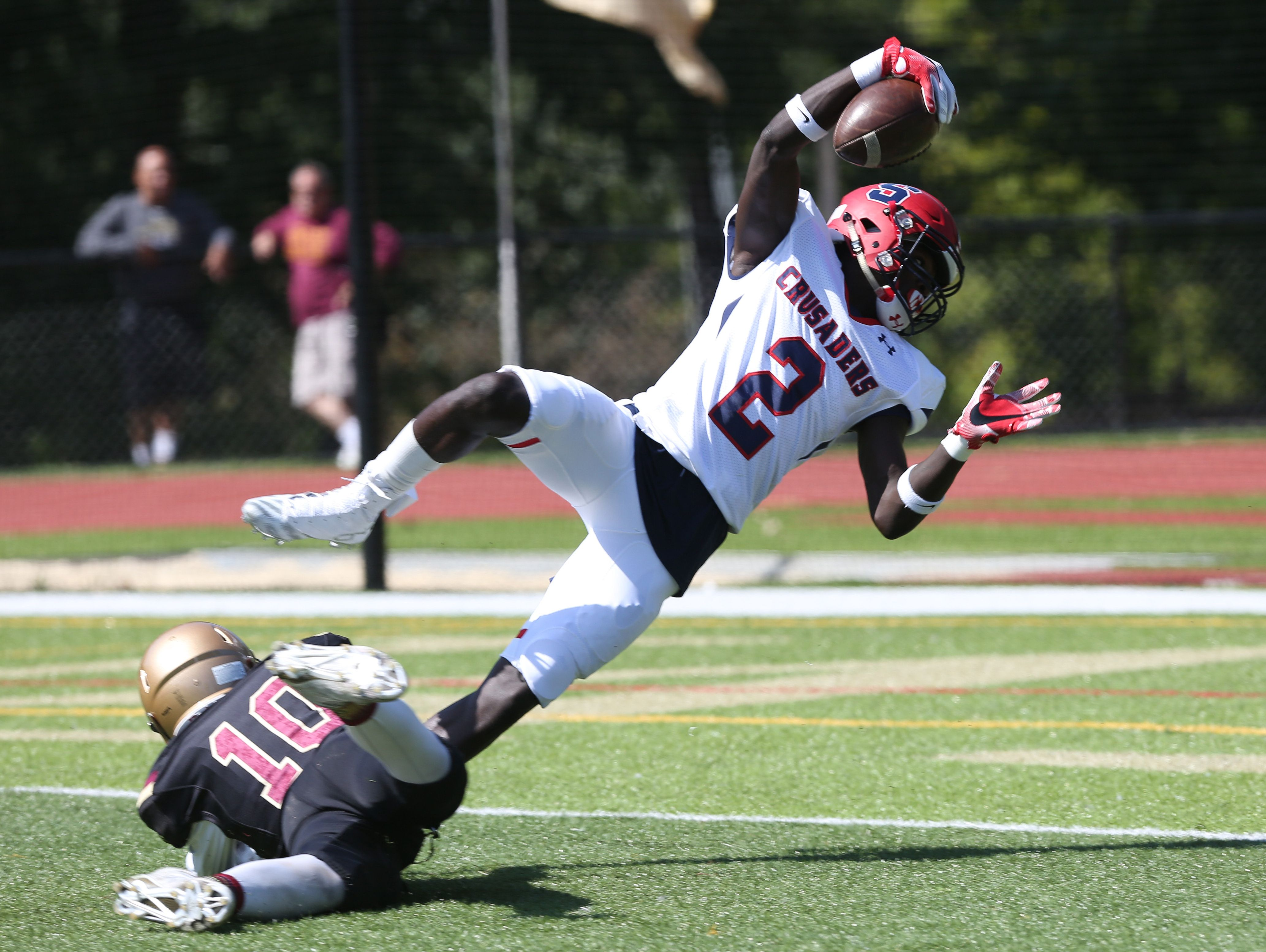 Stepinac's Atrilleon Williams (2) dives into the end zone while being hit by Iona's Michael Degasparis (10) for his first touchdown of the game, during football action at Iona Prep in New Rochelle Sept. 17, 2016. Stepinac won the game 42-34.