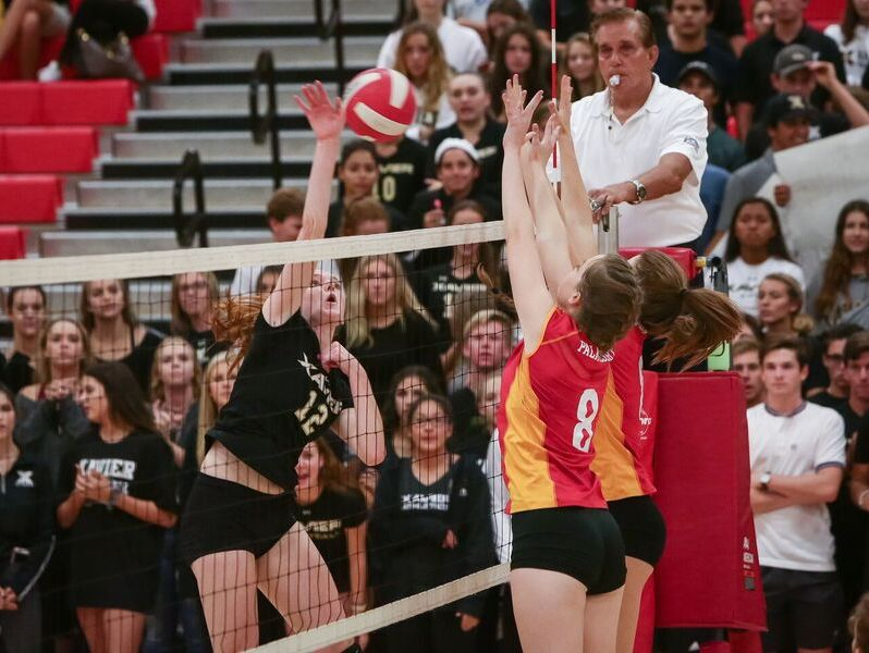 Two Palm Desert blockers rise up to try to stop a spike from the Xavier Prep player.