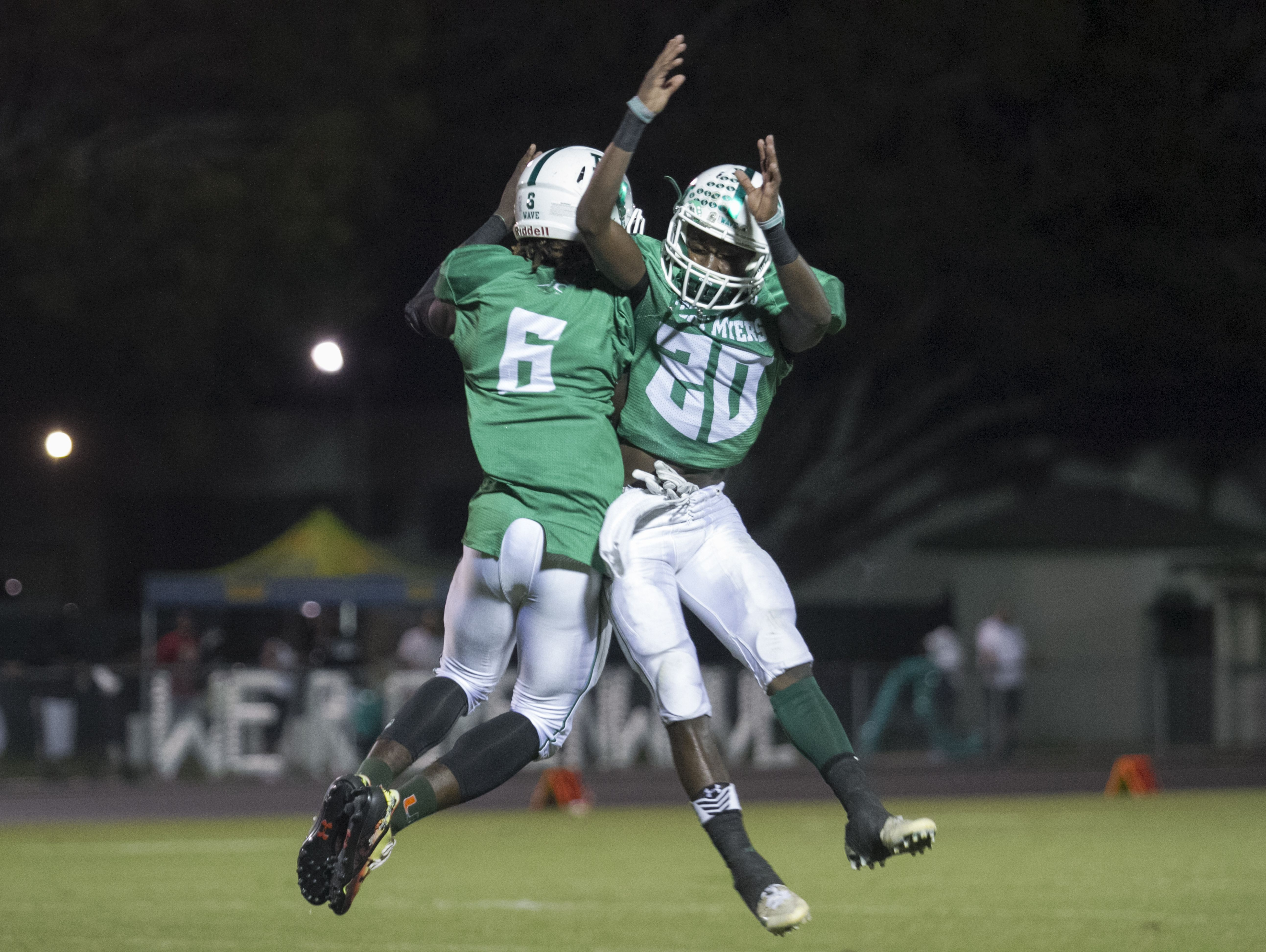 Darrian Felix and Milan Tucker of Fort Myers celebrate the third Green Wave touchdown of the night on Friday, September 30, 2016, against Lehigh Senior High School.