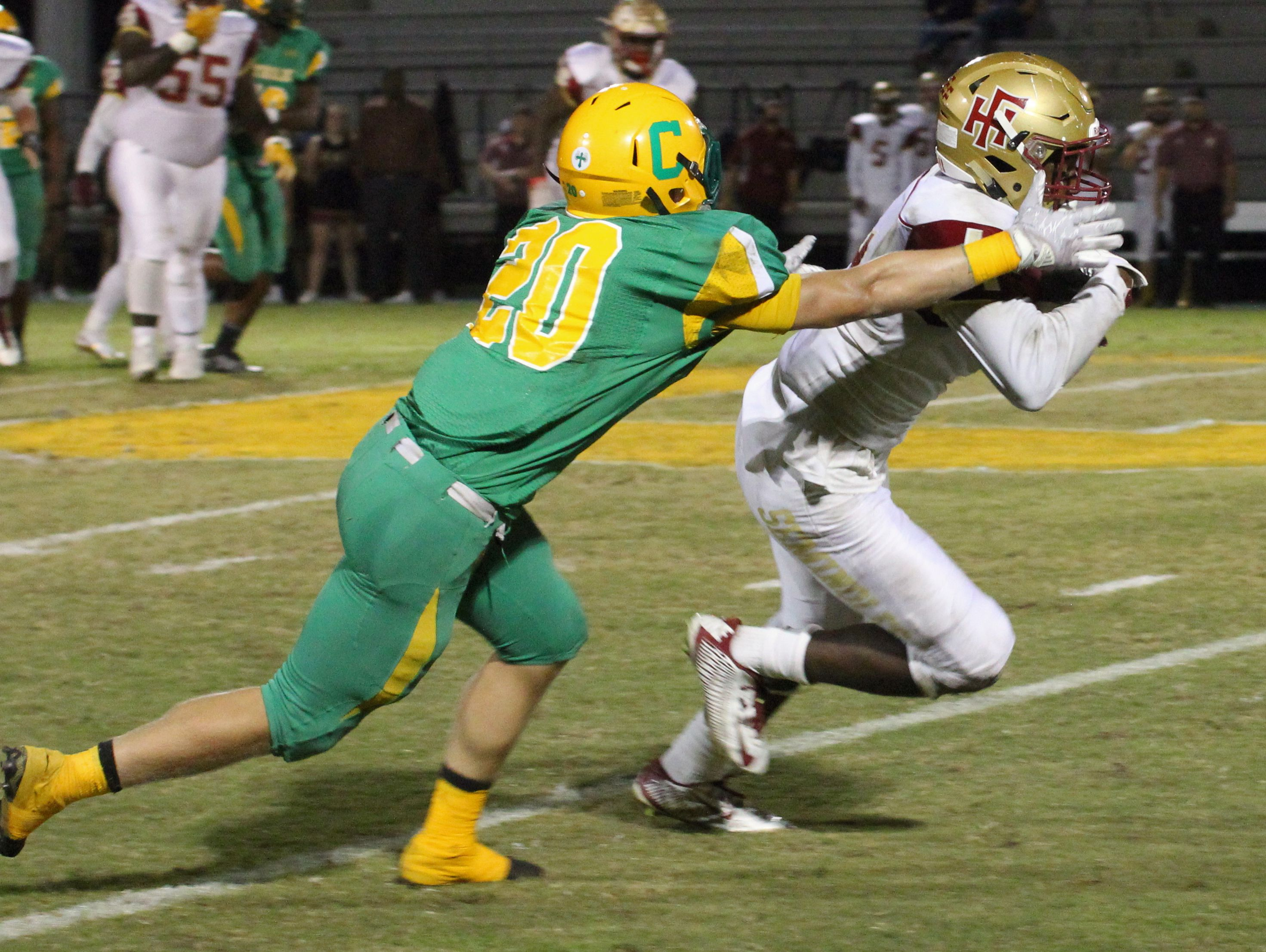 Catholic's Collin Acromite (20) zeros in on Florida High's Kevin Sawyer in first half action.