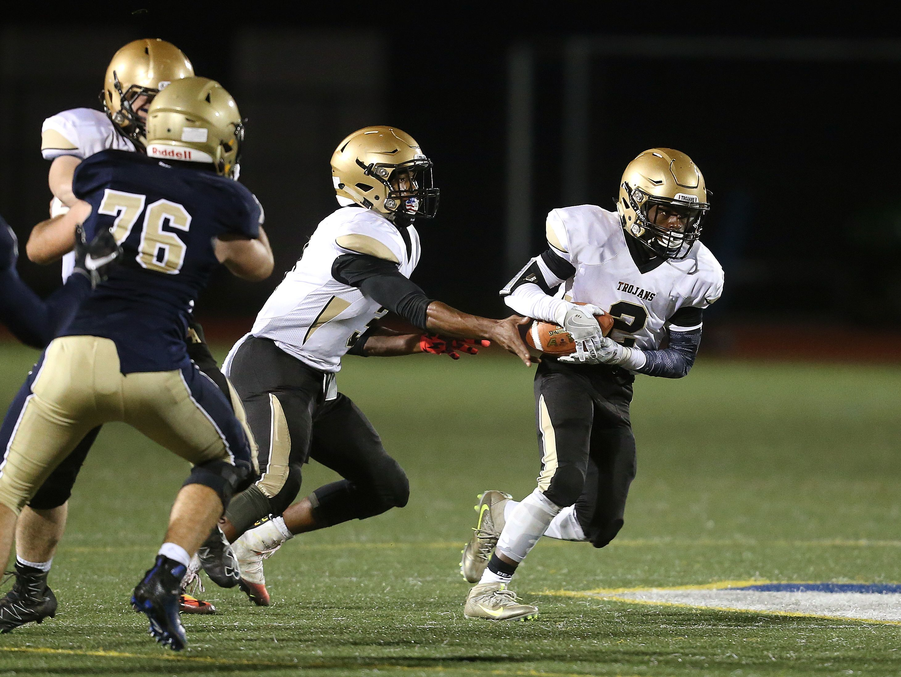 Athena running back Thaj Avies (2) takes a handoff from quarterback Tavon Granison.
