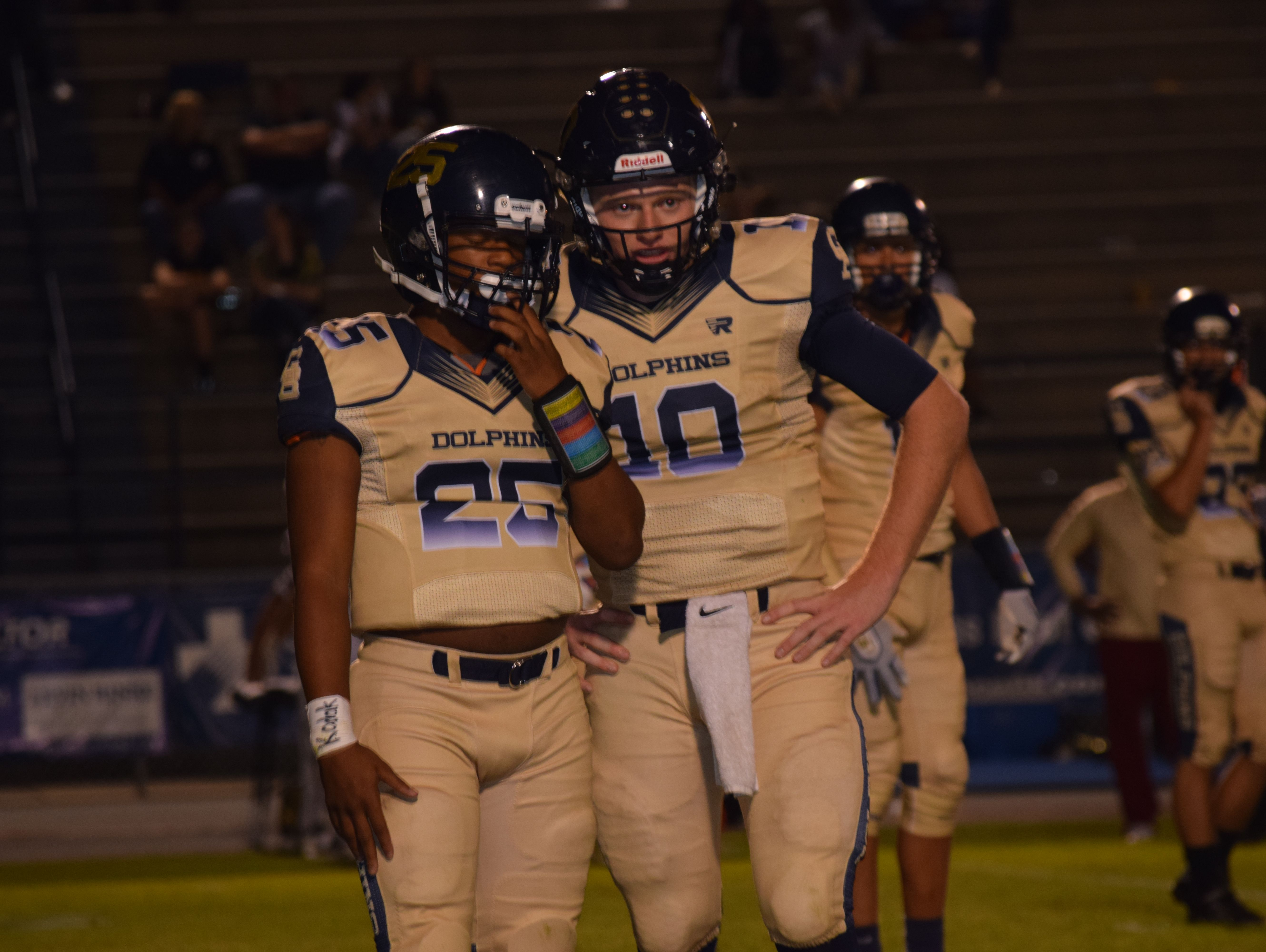 Quarterback Tyler Phelps and tailback Carl Taylor discuss play during Dolphins' 36-3 homecoming win Friday night.