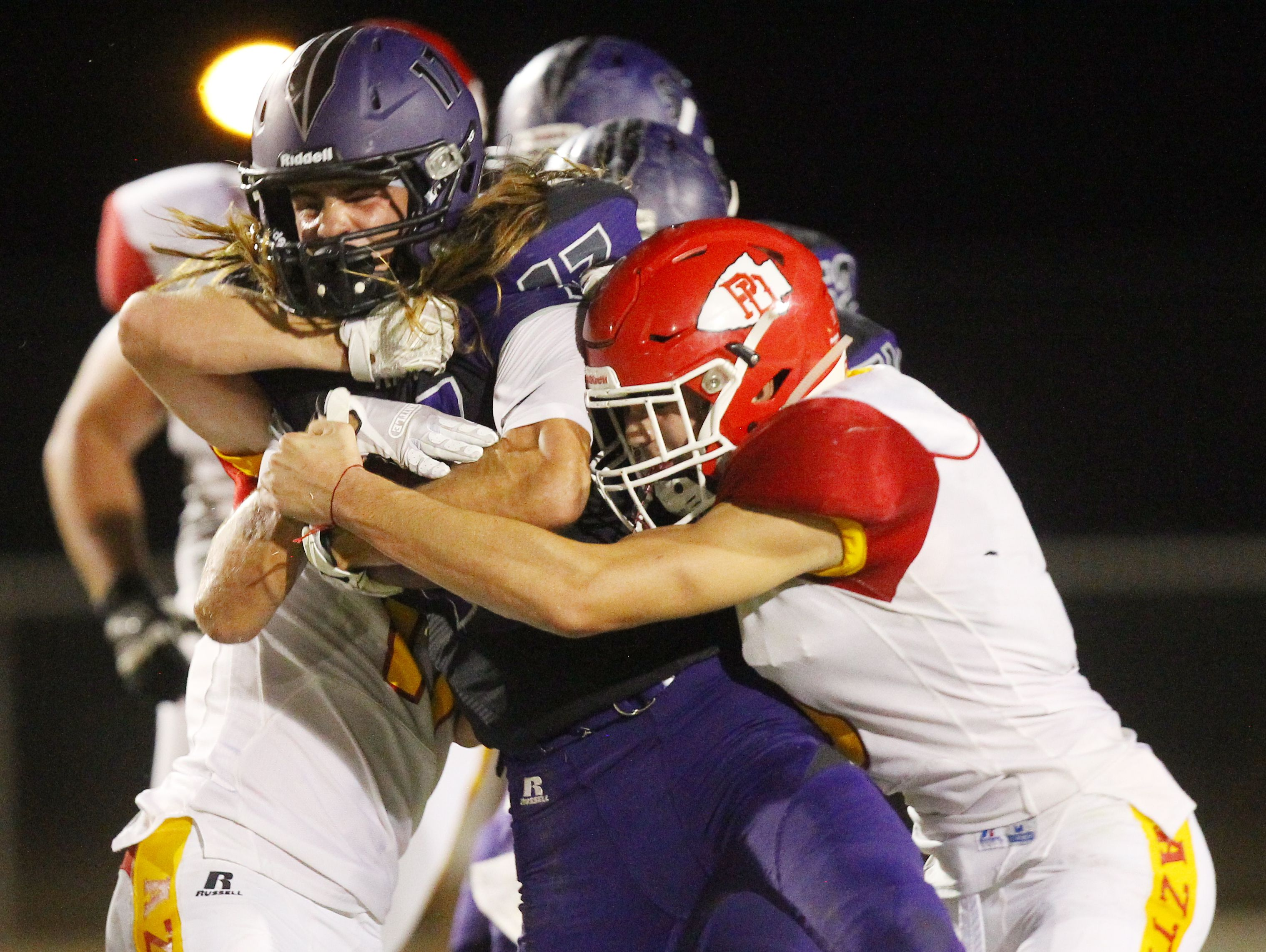 Shadow Hills High School's Jason JD Lang runs for yardage as several Palm Desert High School defender make an attempt to bring him down during their game at Indio.