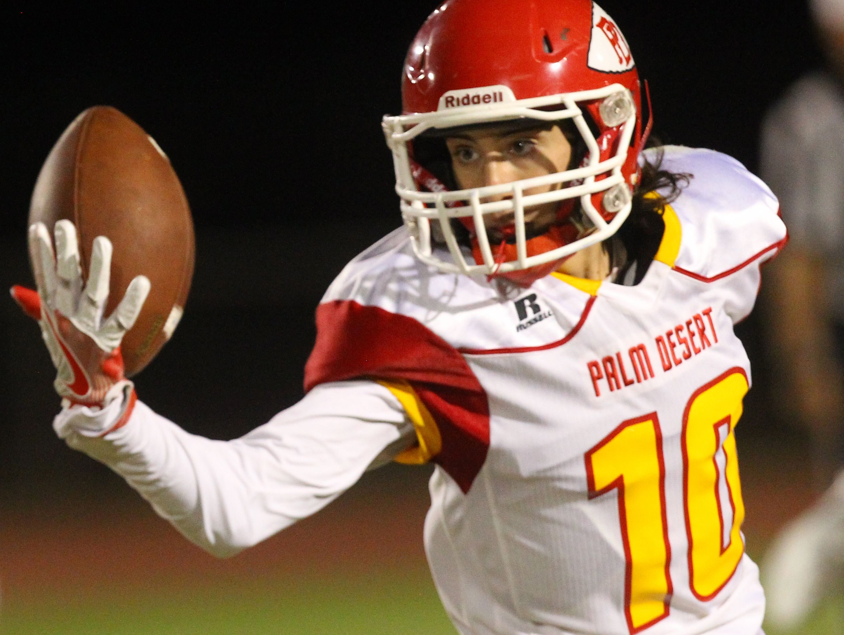 Palm Desert High School's #10 makes an attempt to catch a pass with one hand but fails during their visit to Shadow Hills High School in Indio.