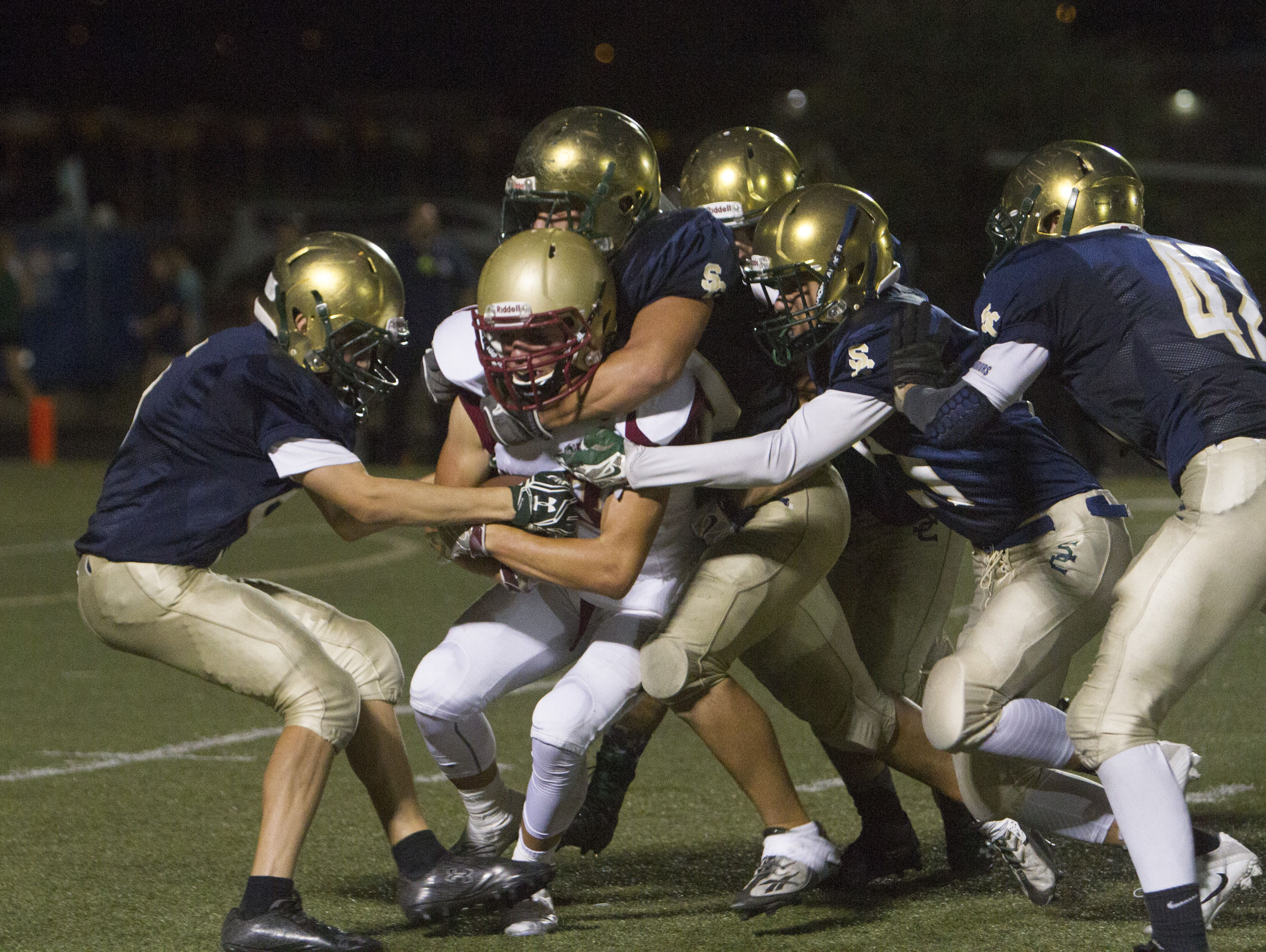 Snow Canyon defensive players hold back a Cedar High runner during their game Friday, Sept. 30, 2016.