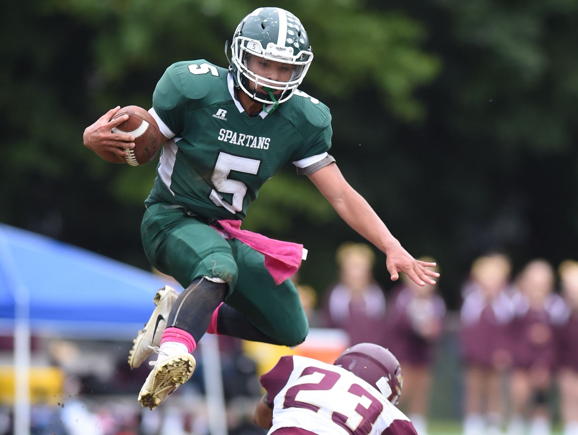 Spackenkill's Camron Abalos jumps over O'Neill's James Matautia during Saturday's game at Spackenkill.