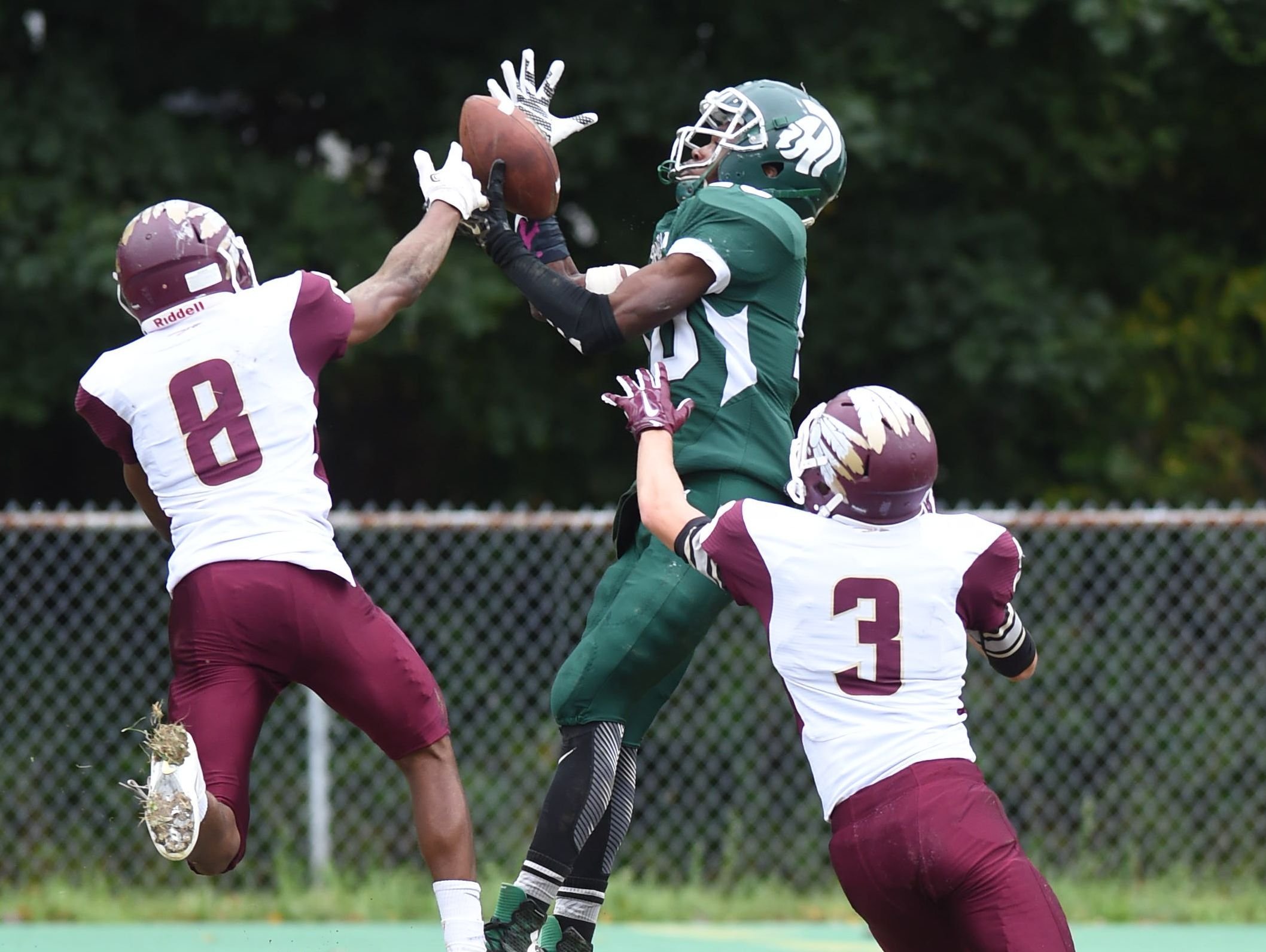 Spackenkill's Kabongo Barry makes a flying catch between O'Neill's, from left, Joel Baskerville and Tully Boylan during Saturday's game at Spackenkill.