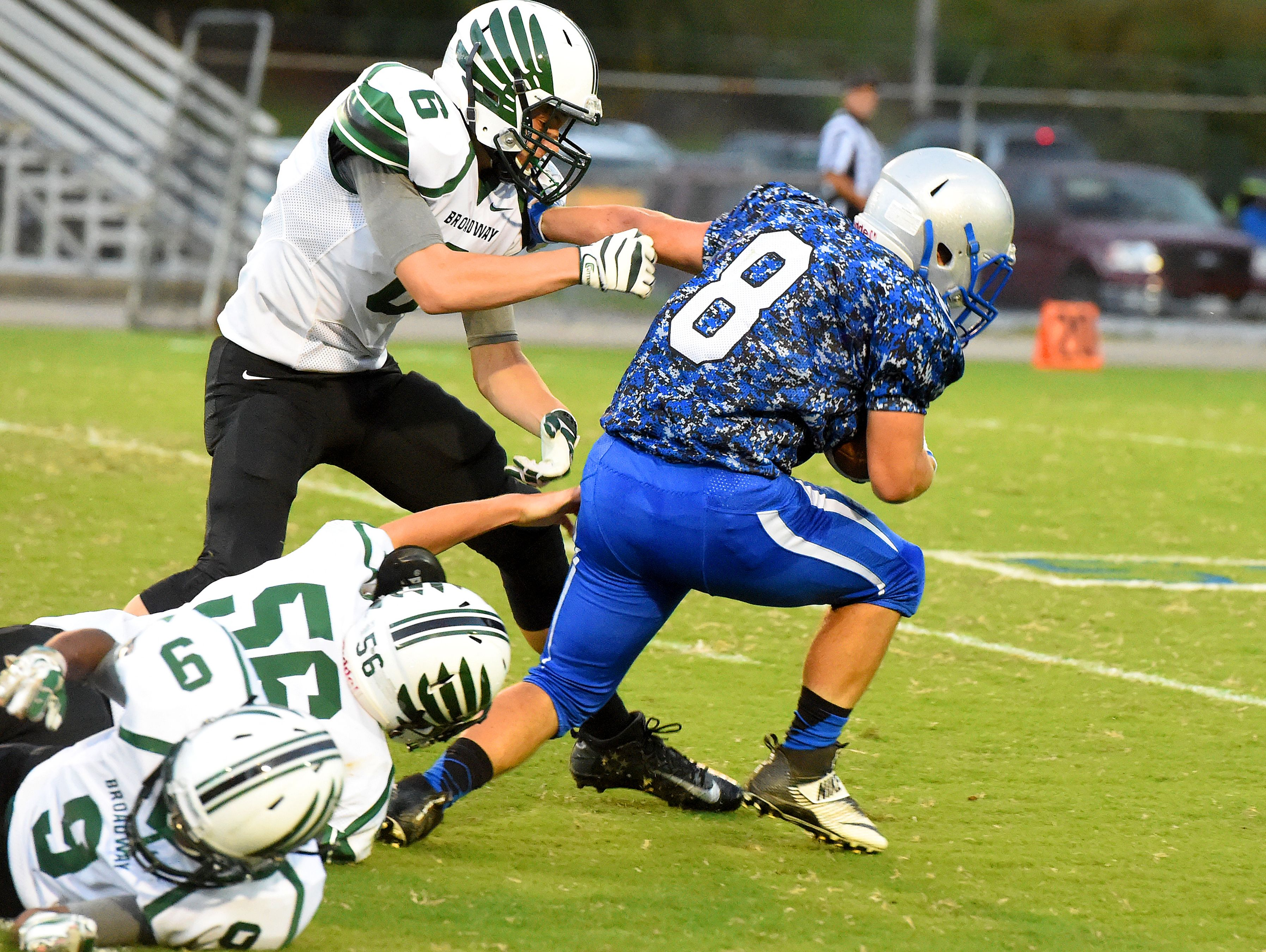 Robert E. Lee's Garrett Lawler fights to break a tackle by Broadway's Christopher Jacobs, Michael Fewell and Caleb Williams during a football game played in Staunton on Monday, Oct. 3, 2016.