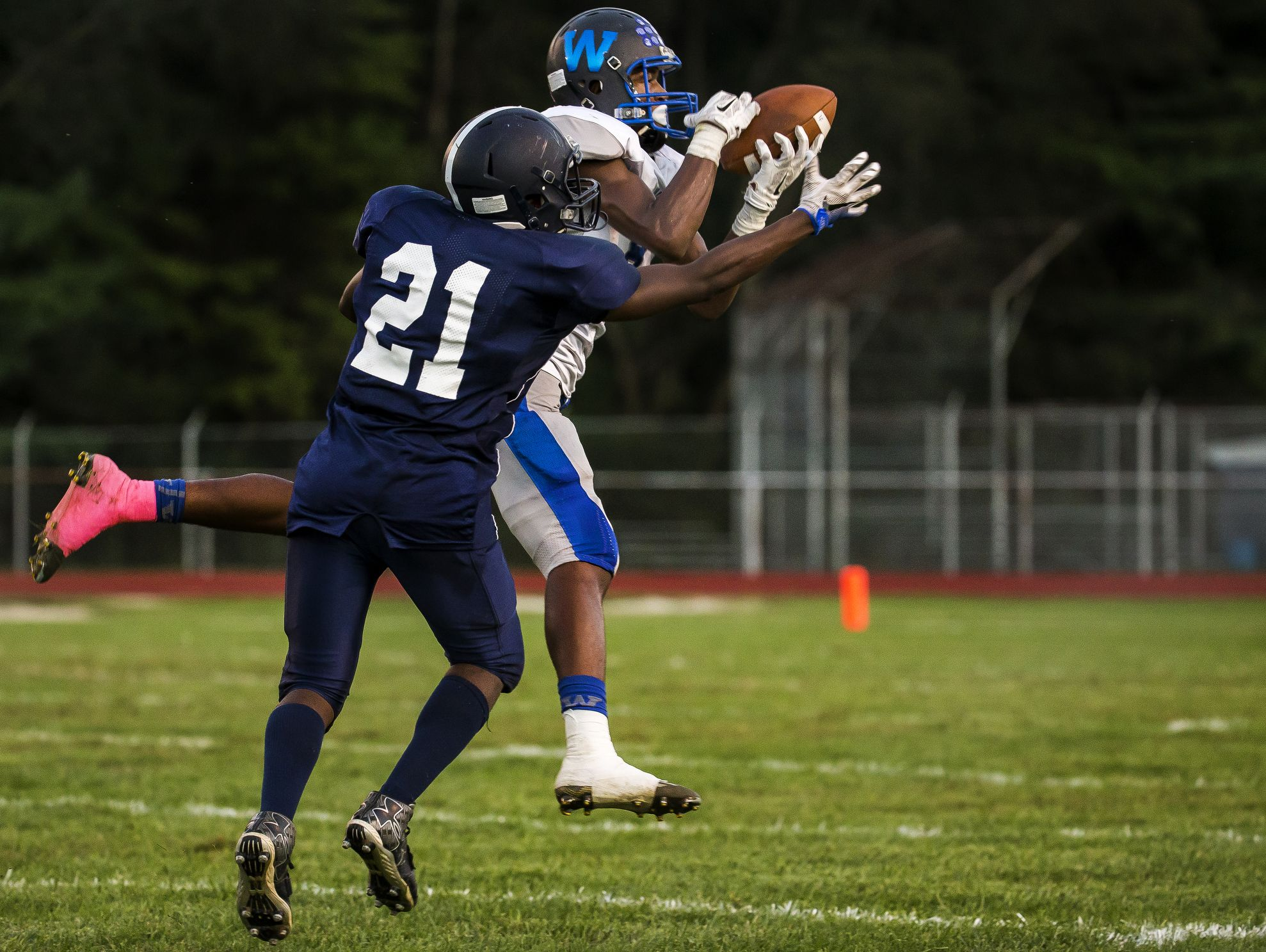 Woodbridge's Jamon Kane intercepts a pass intended for Lake Forest's Ondre Sheppard (No. 21) in the second quarter of Woodbridge's 32-0 win over Lake Forest at Lake Forest High School in Felton on Monday evening. Kane returned the interception for a touchdown.