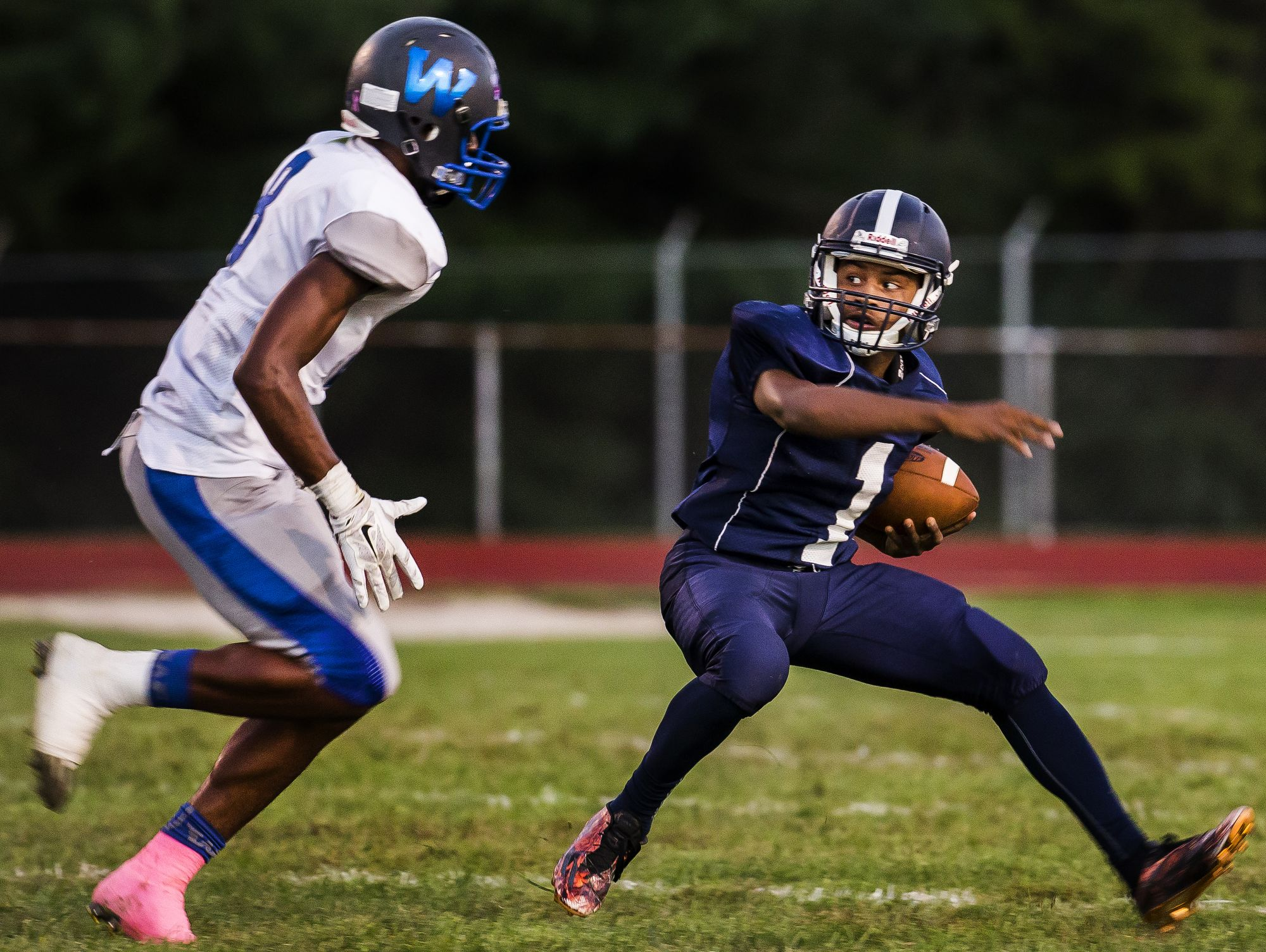 Lake Forest quarterback Xavier Daniels (No. 1) as Woodbridge's Jamon Kane closes in on him in the second quarter of Woodbridge's 32-0 win over Lake Forest at Lake Forest High School in Felton on Monday evening.