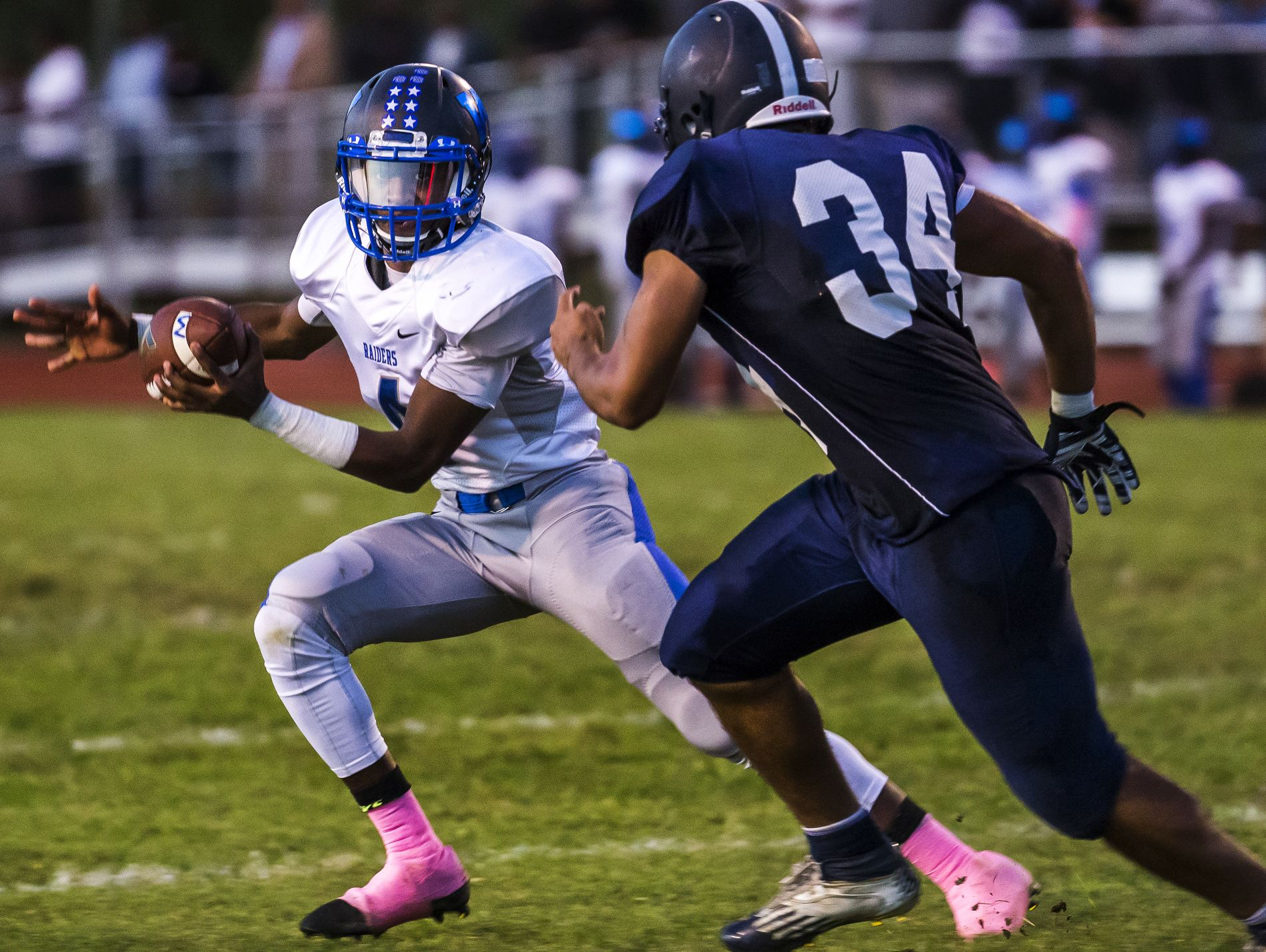 Woodbridge quarterback Troy Haynes tries to evade Lake Forest's Kobe Mumford (No. 34) in the second quarter of Woodbridge's 32-0 win over Lake Forest at Lake Forest High School in Felton on Monday evening.