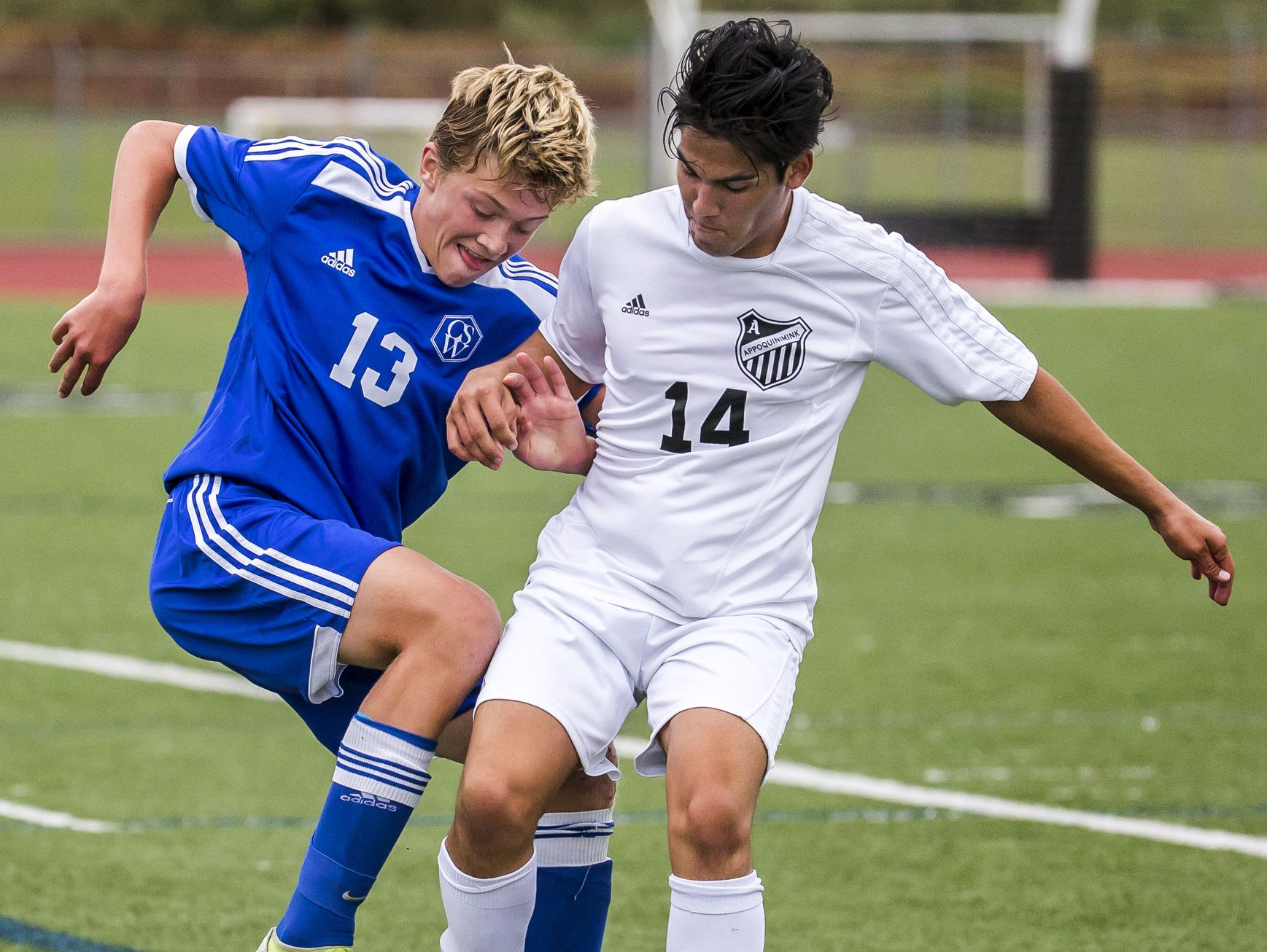 Charter's Graeme Newcombe (No. 13) fights the ball away from Appoquinimink's Jose Hilario (No. 14) in the second half of Appoquinimink's 1-0 win over Charter School of Wilmington at Appoquinimink High School in Middletown on Tuesday afternoon.