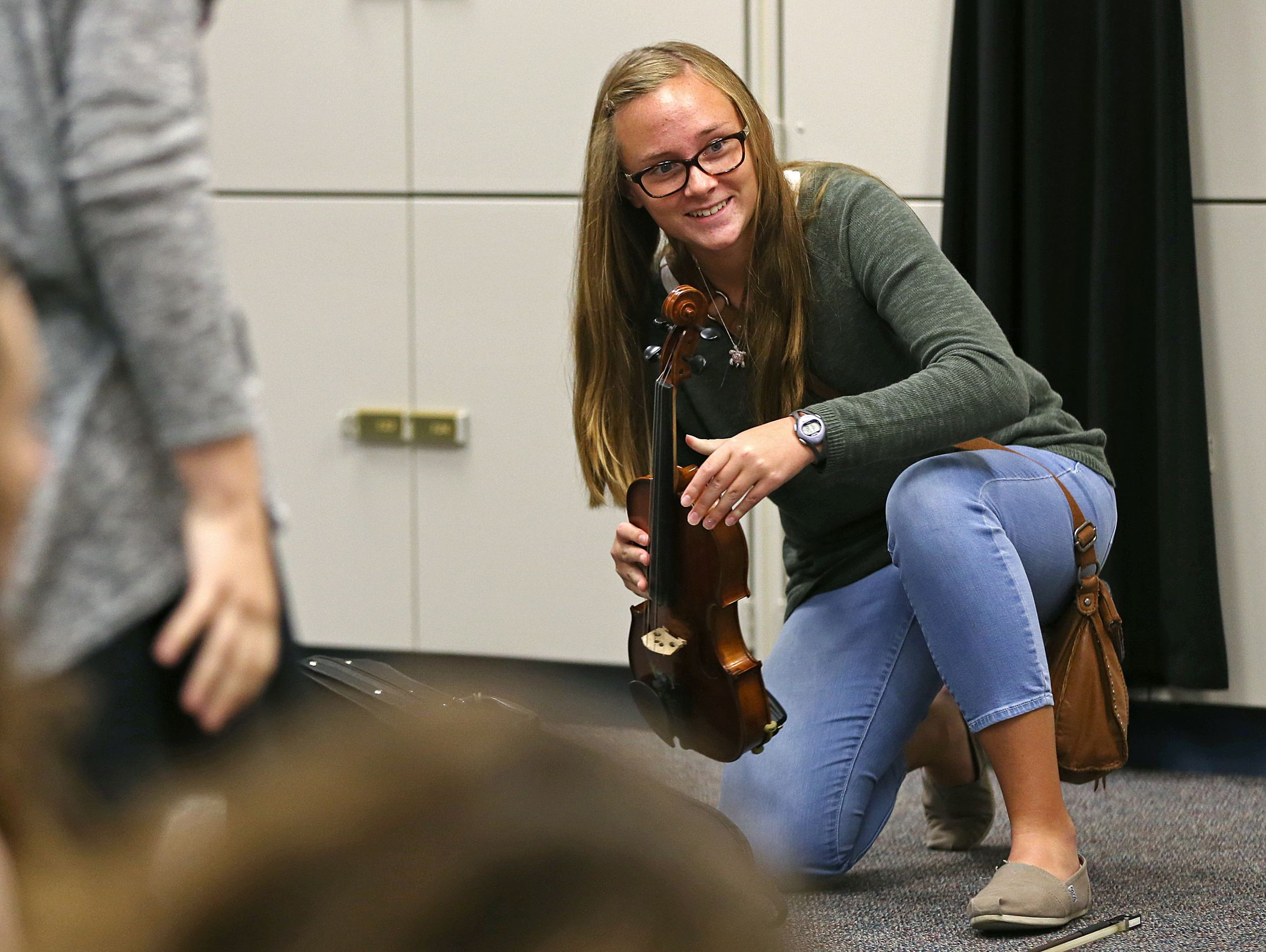 Caroline Kavanaugh chats with friends before rehearsal for an orchestra concert during the school day at Perry Meridian High School, Tuesday, October 4, 2016.
