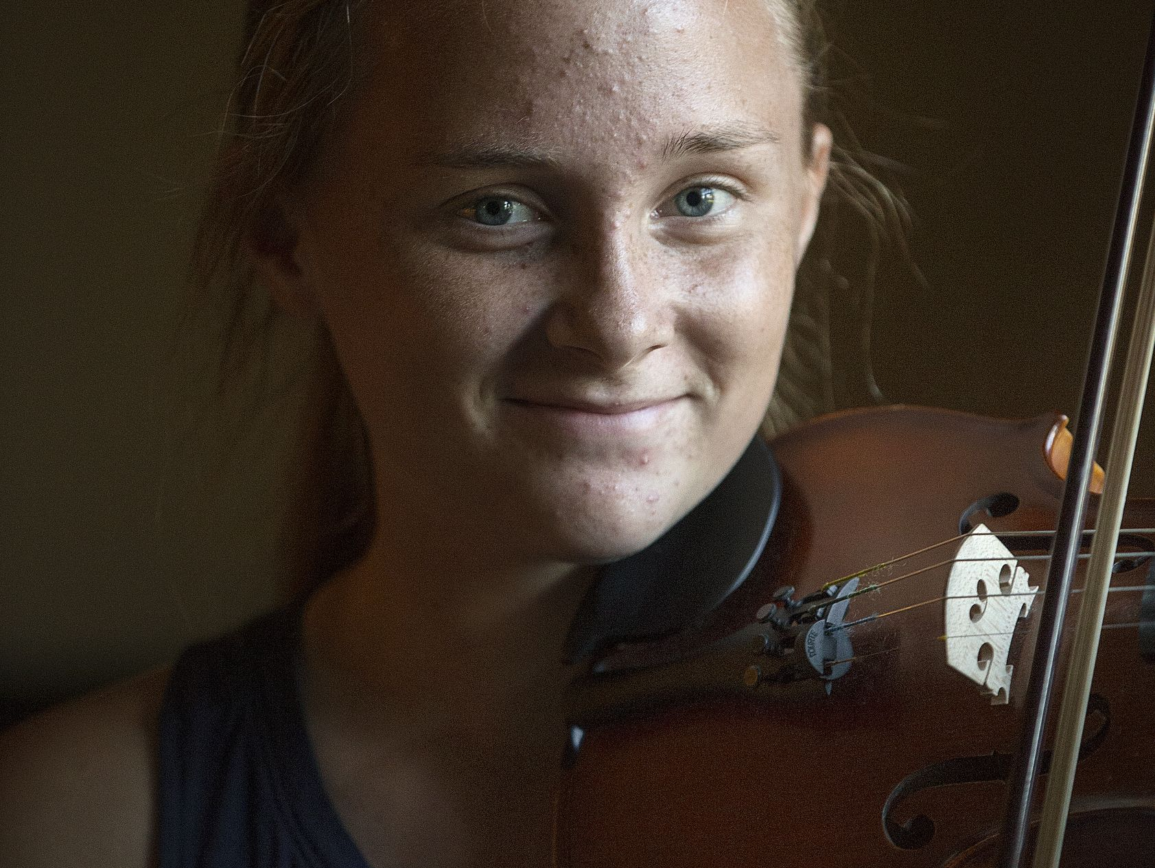 Caroline Kavanaugh poses with her violin for a portrait at her family's south side home, Despite the challenge of living with a brain tumor since her diagnosis in fourth grade, Kavanaugh stays involved in her many passions.