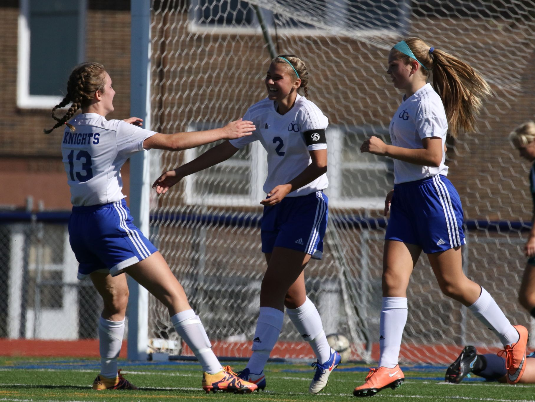 Izzy Hedge (2) of O'Gorman celebrates with Ashlee Beacom (13) and Katelyn Rush (4) after her second goal against Pierre during Wednesday's semi-final.