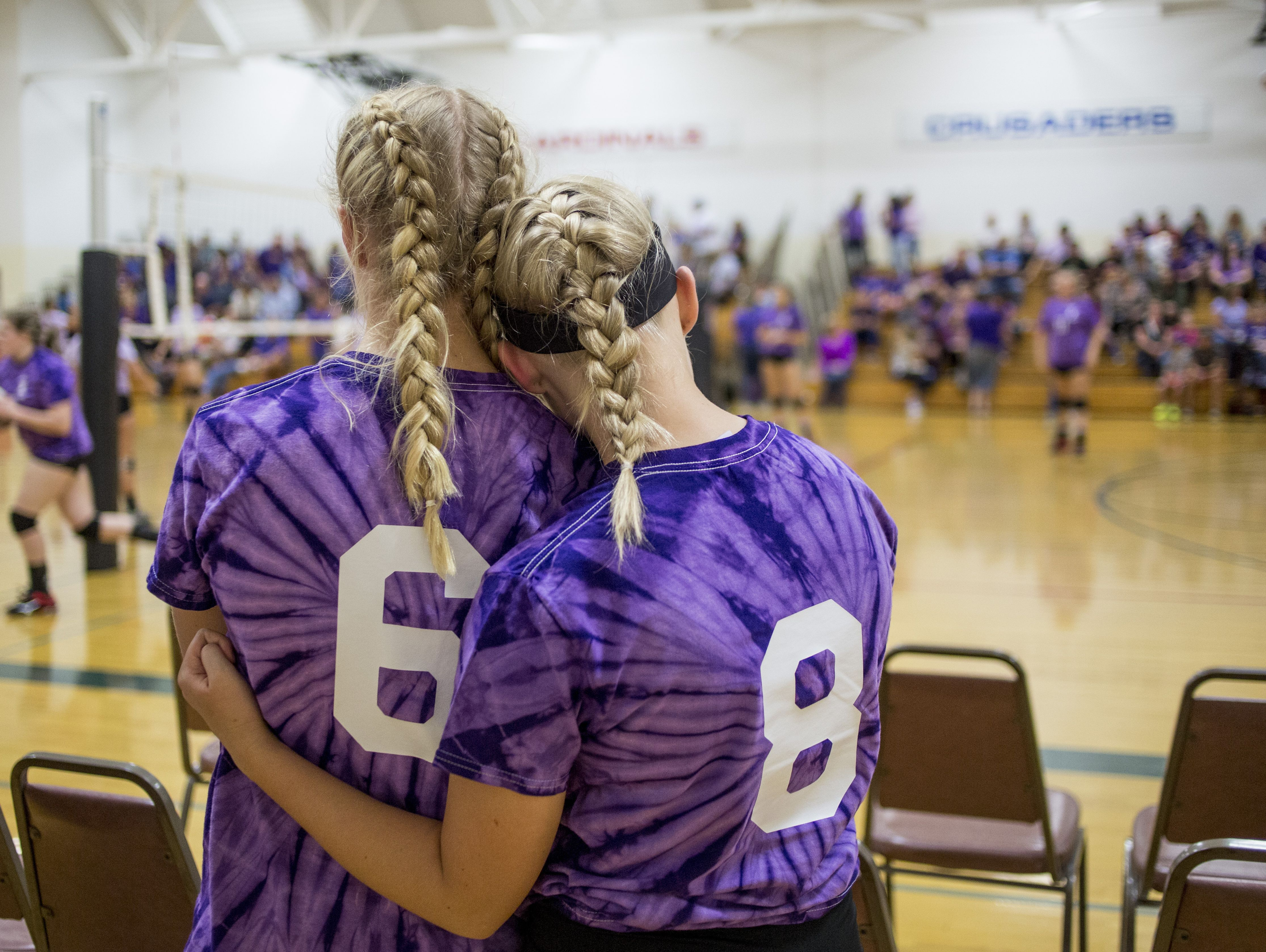 Junior varsity players Lauren Luzynski and Alexis Carriere hug before a volleyball game Wednesday, Oct. 5, 2016 at Cardinal Mooney High School.