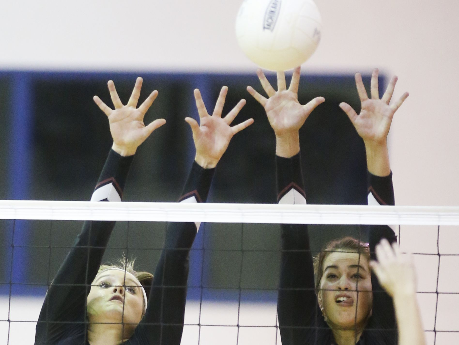 Appoquinimink's Carly Burns (12) and Taylor Modica leap to try to block a kill attempt by Middletown's Devin Huisenga in the second game of the Jaguars' 3-0 win at Middletown High Wednesday.