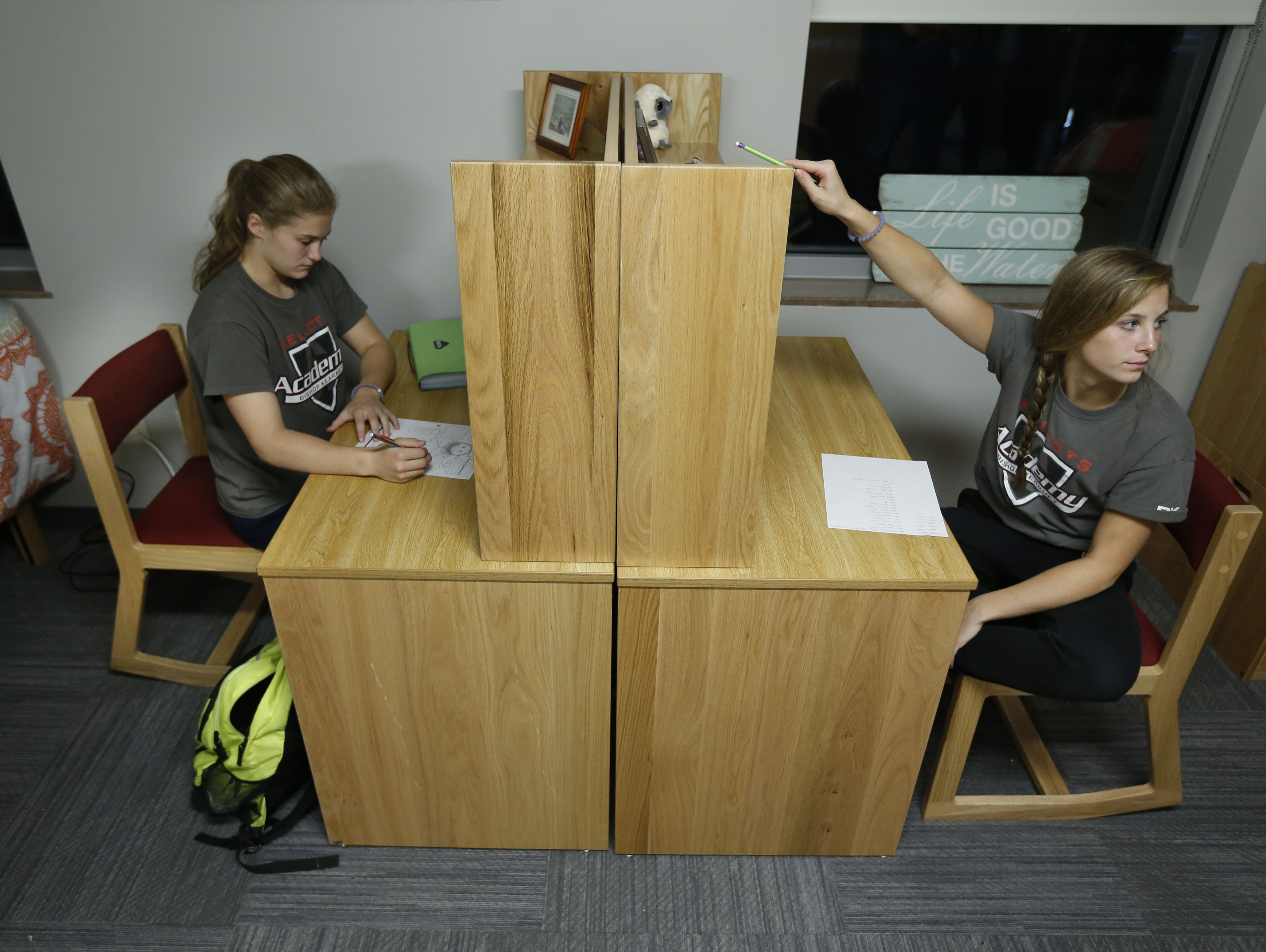 Twins Mia and Maddy Coene of the Bishop Kearney Selects Academy girls hockey team, work at the desks in their bedroom.