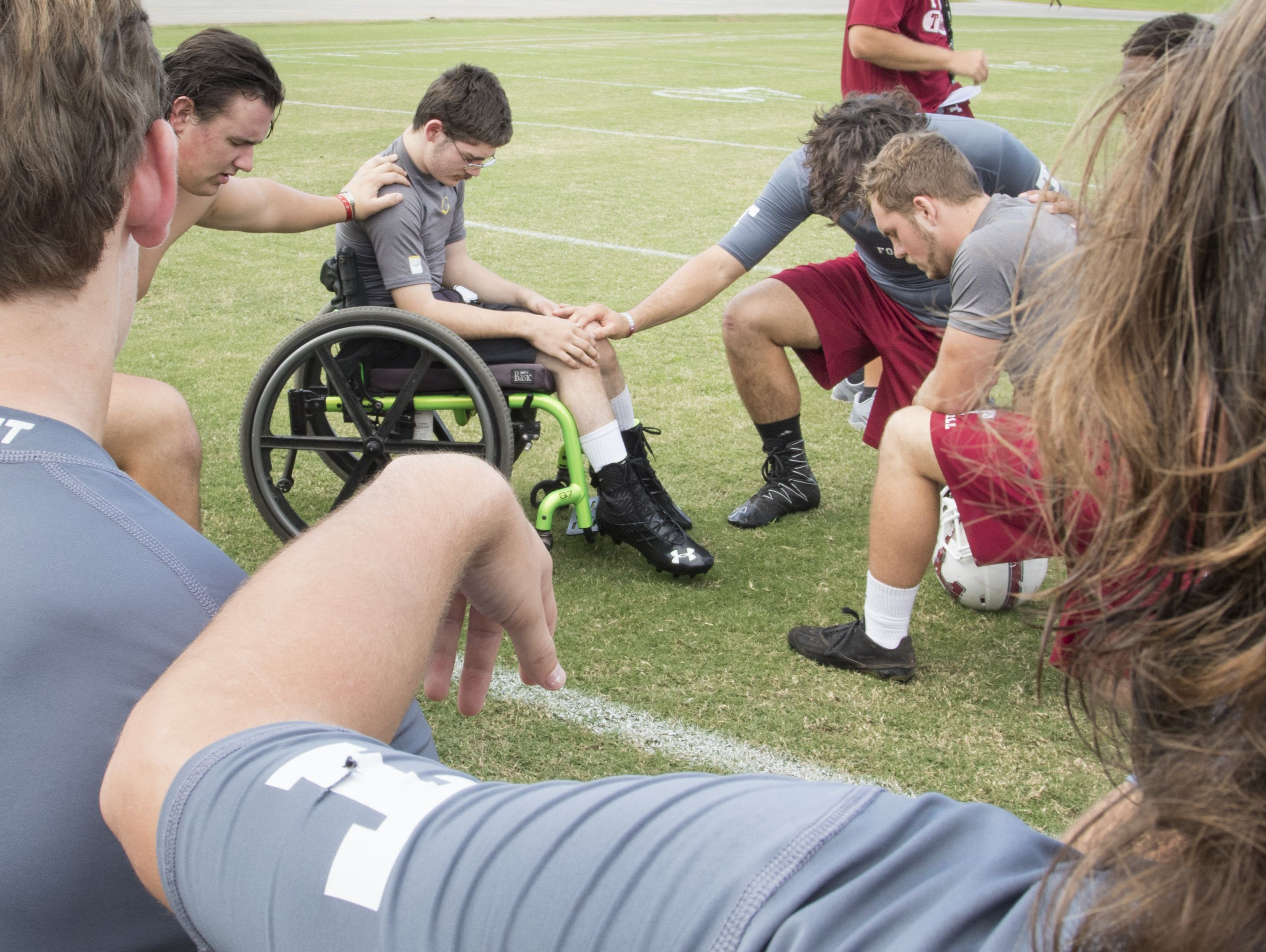 Markus Baxley, a student with cerebral palsy, joins his teammates in a prayer following football practice at Tate High School in Pensacola on Thursday, October 6, 2016. Baxley will fulfill a lifelong dream when he participates in one play in the Friday night game against Pace High School.