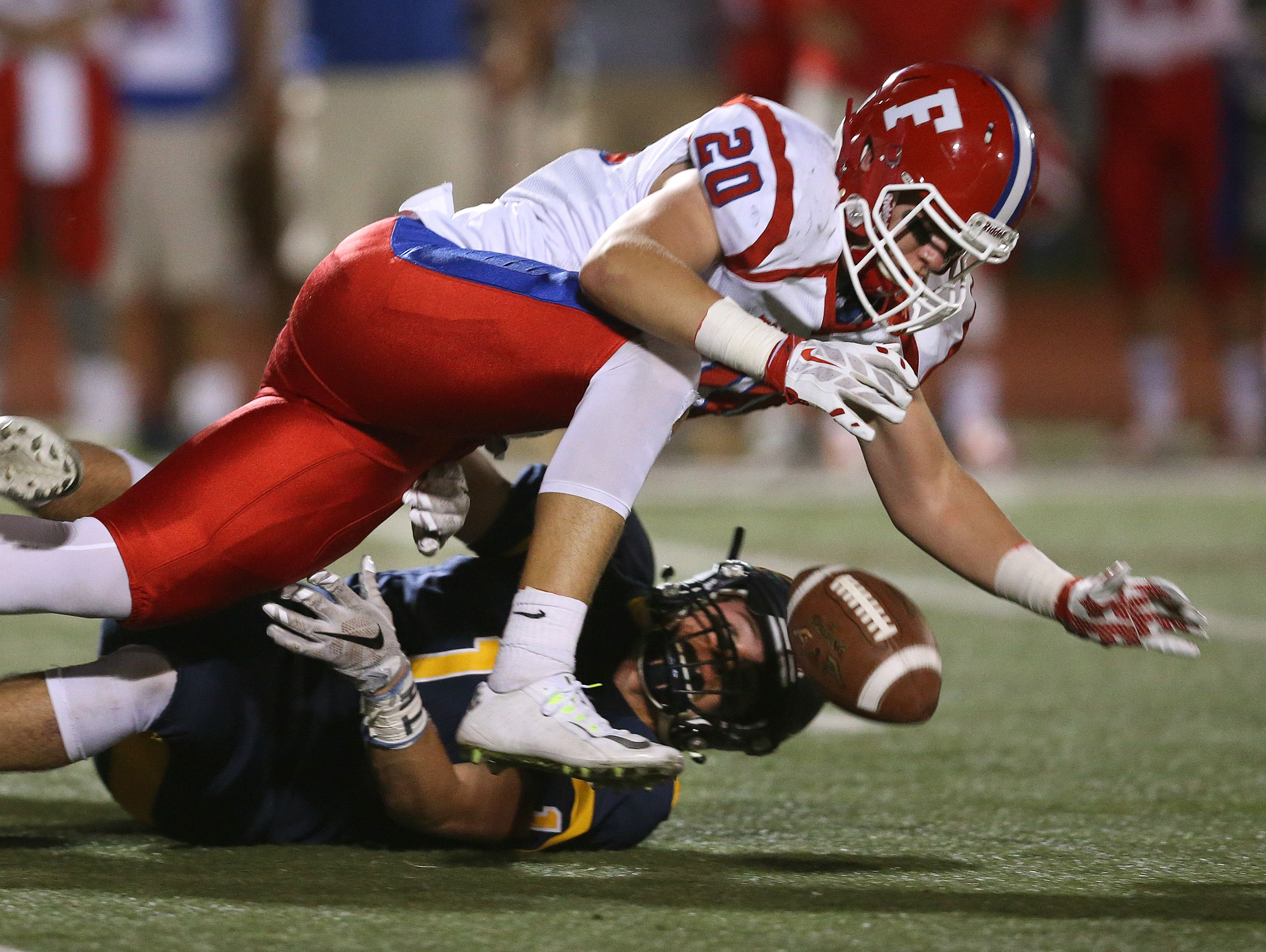 Fairport running back Michael Kozar (20) is tackled by Victor's Mitchell Cain (1). Kozar was ruled down by contact before the fumble.