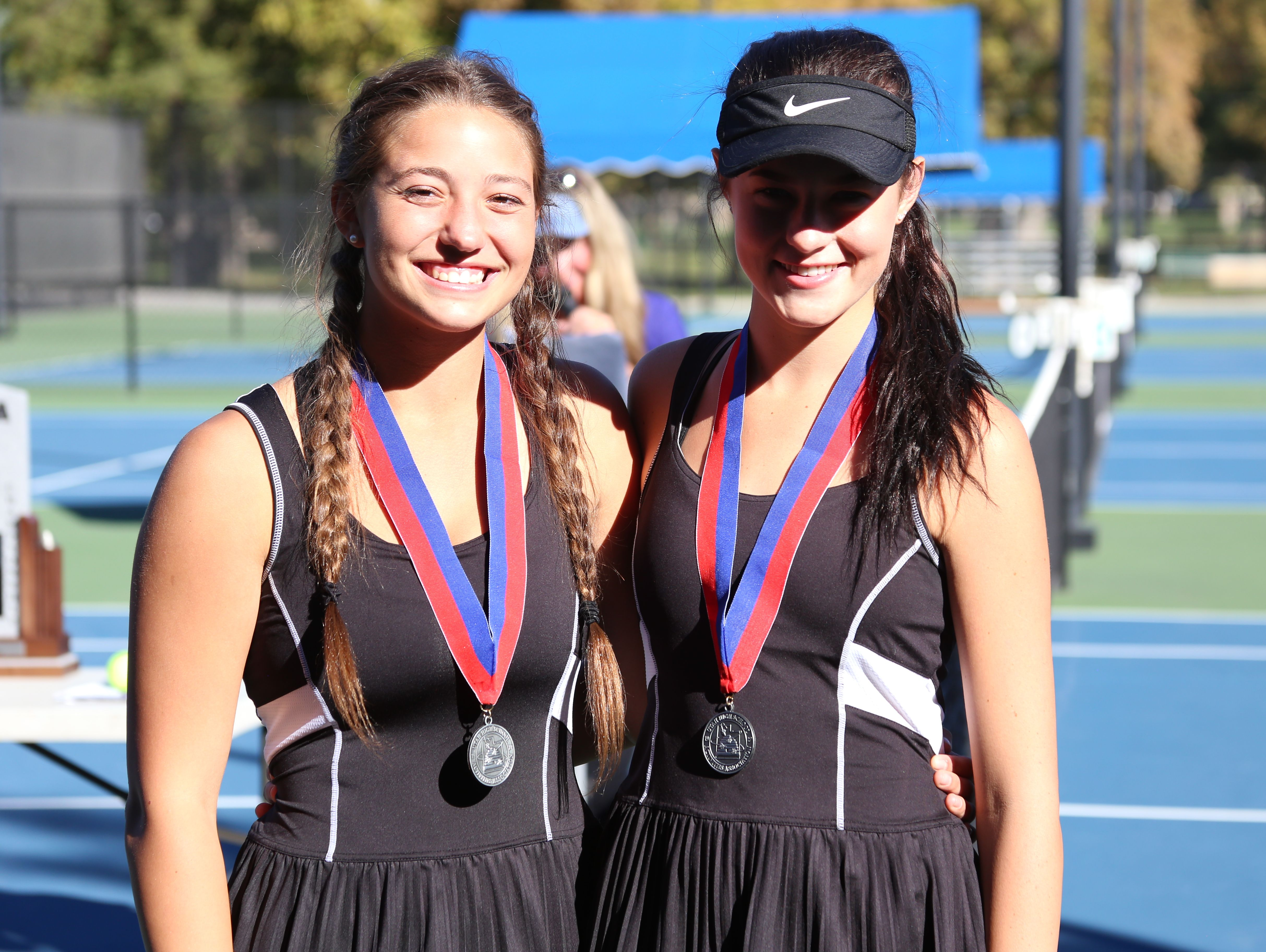 Desert Hills' Alani Plumb and Allie Beck pose for a picture after taking second in first doubles at the 2016 3A state tournament at Liberty Park on Friday.