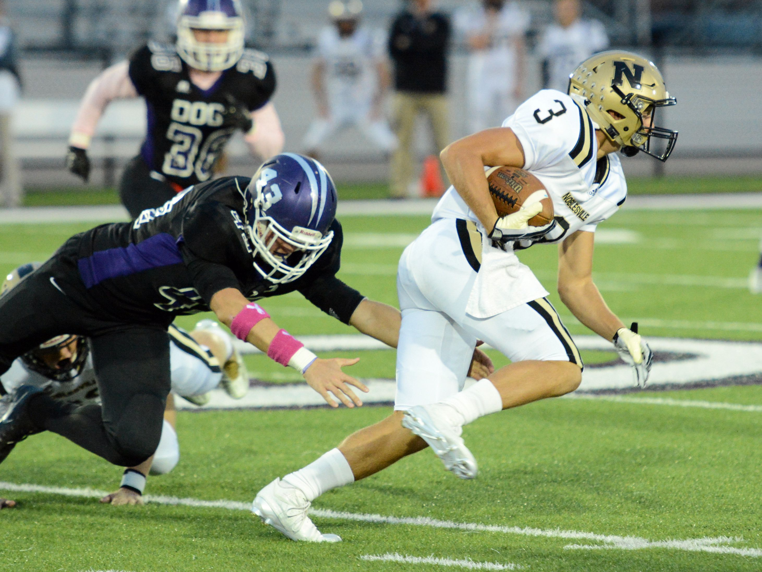 Noblesville's Nick Rusie eludes a Brownsburg defender during the Millers' 22-21 win Friday night.