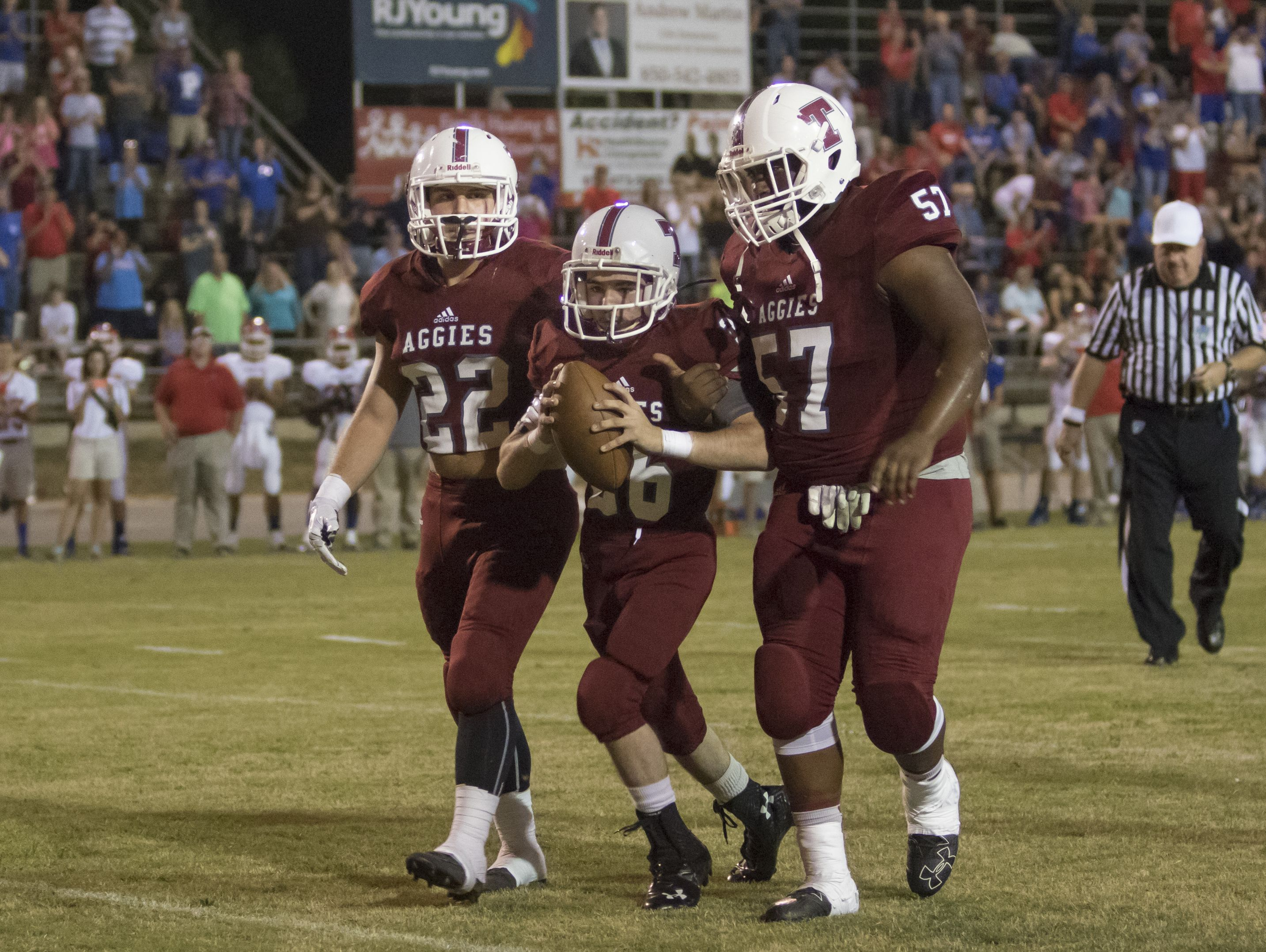 Jake Henry (16) hands off to honorary football player Markus Baxley(26), a student with cerebral palsy, as teammates Dylan Foxhall (22) and Evan Allen (57) carry him to a touchdown prior to the game against Pace High School in Pensacola on Friday, October 7, 2016.
