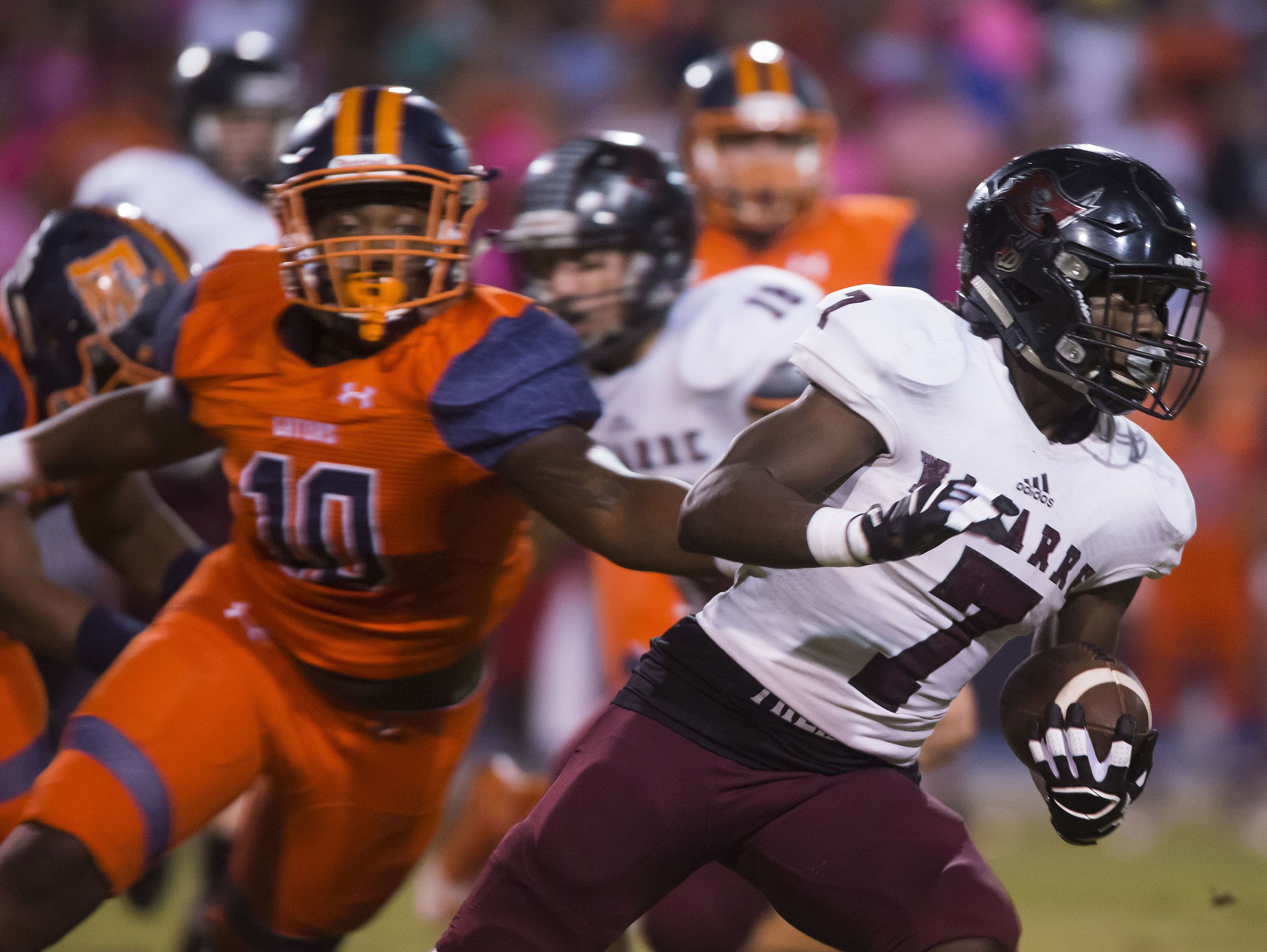 Navarre High School's, Michael Carter, (No. 7) gives the Escambia High School defense the slip with a run up the middle during Friday night's game against the Gators.