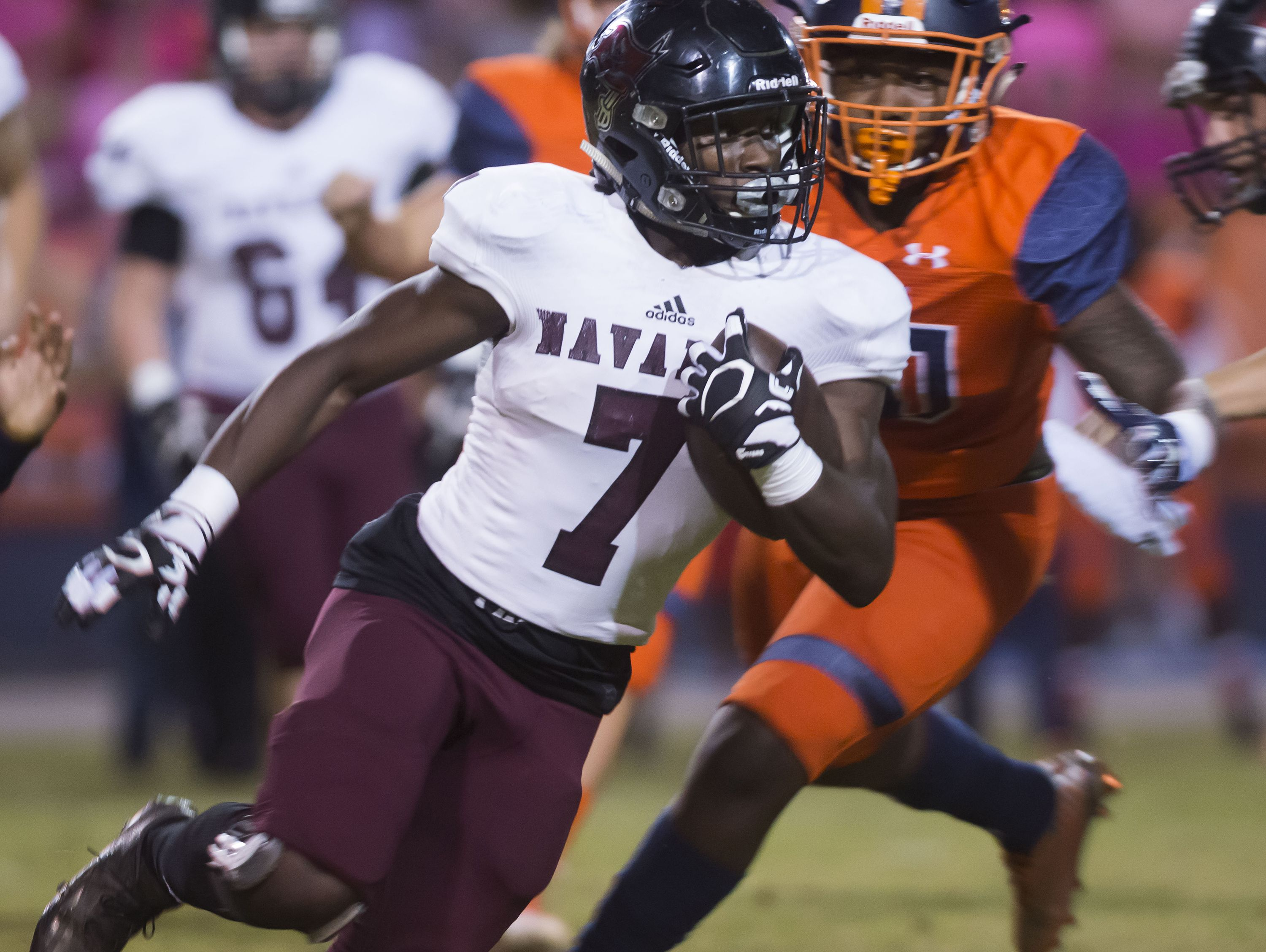 Navarre High School's, Michael Carter, (No. 7) tries to give the Escambia High School defense the slip with a run to the outside during Friday night's game against the Gators.