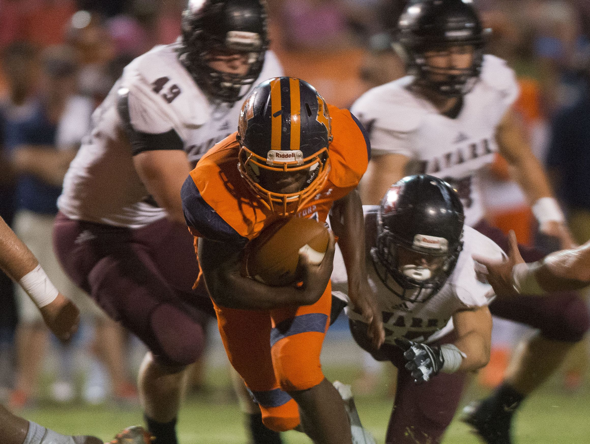 Escambia High School running back, Antonio Benjamin, (No. 3) breaks the tackles of the Navarre High School defense during Friday's game against the Raiders.