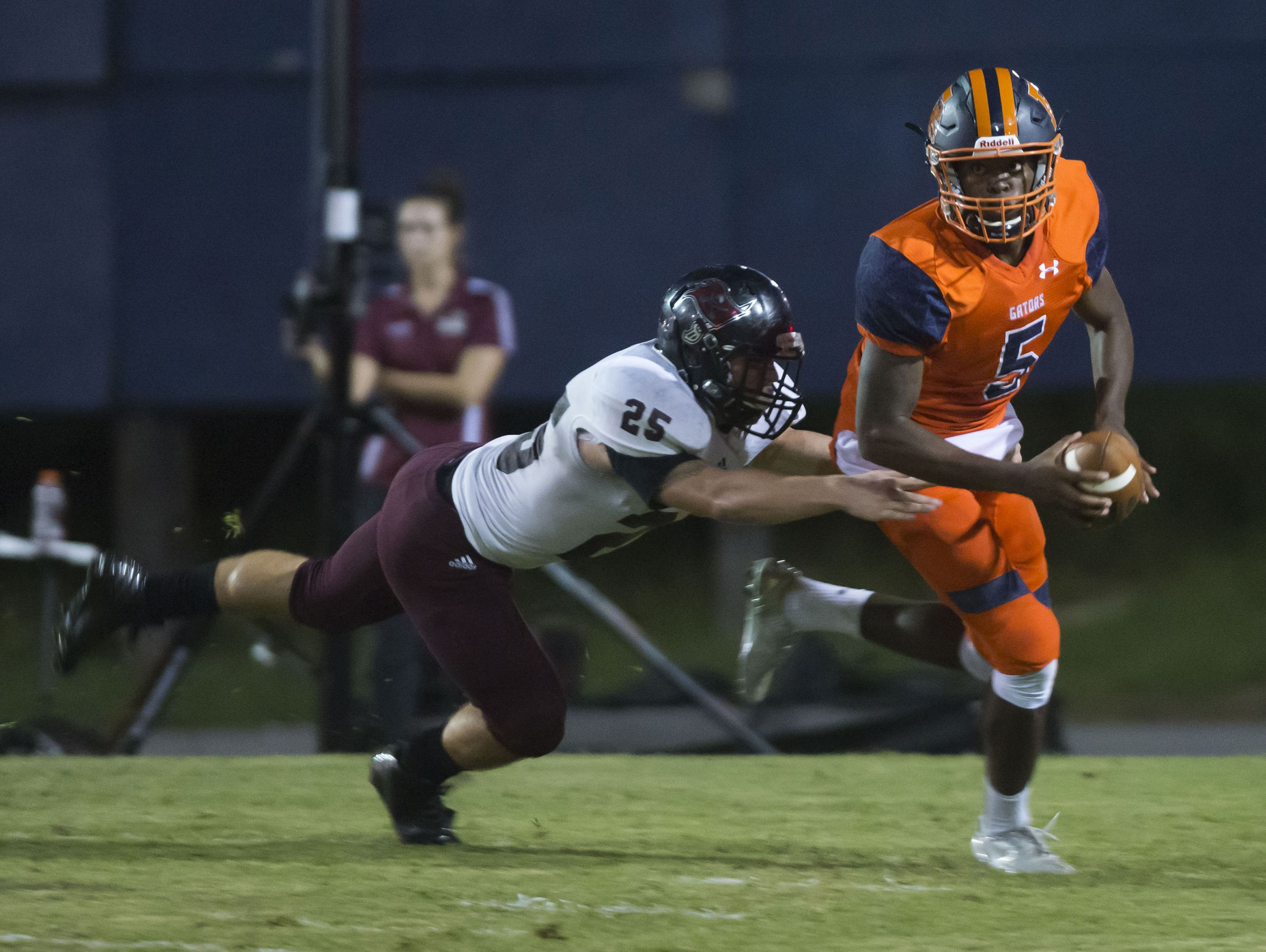 Navarre High School linebacker, Xavier Fernandez, (No. 25) wraps up Escambia High School quarterback, Av Smith, (No. 5) behind the line of scrimmage up by during Friday night's game.