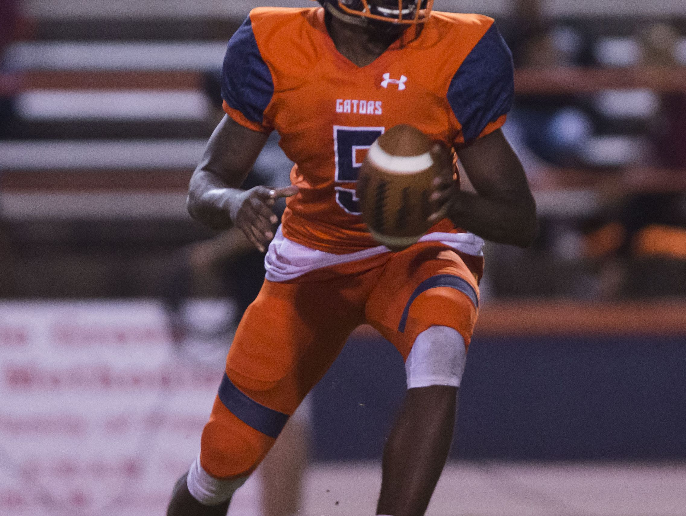 Escambia High School quarterback, Av Smith, (No. 5) prepares to pitch the ball to an approaching running back during Friday night's game against Navarre High School.