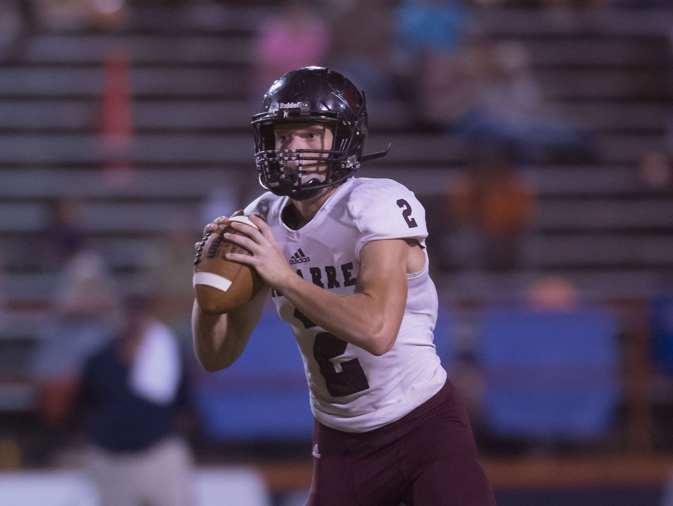 Navarre High School quarterback, Caine Adamson, (No. 2) rolls out of the pocket in search of an open receiver during Friday night's game against Escambia High School.