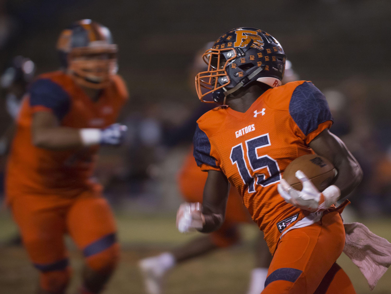 Escambia High School's Steven McGhee, (No. 15) runs through the Navarre High School defense during Friday night's senior night game.