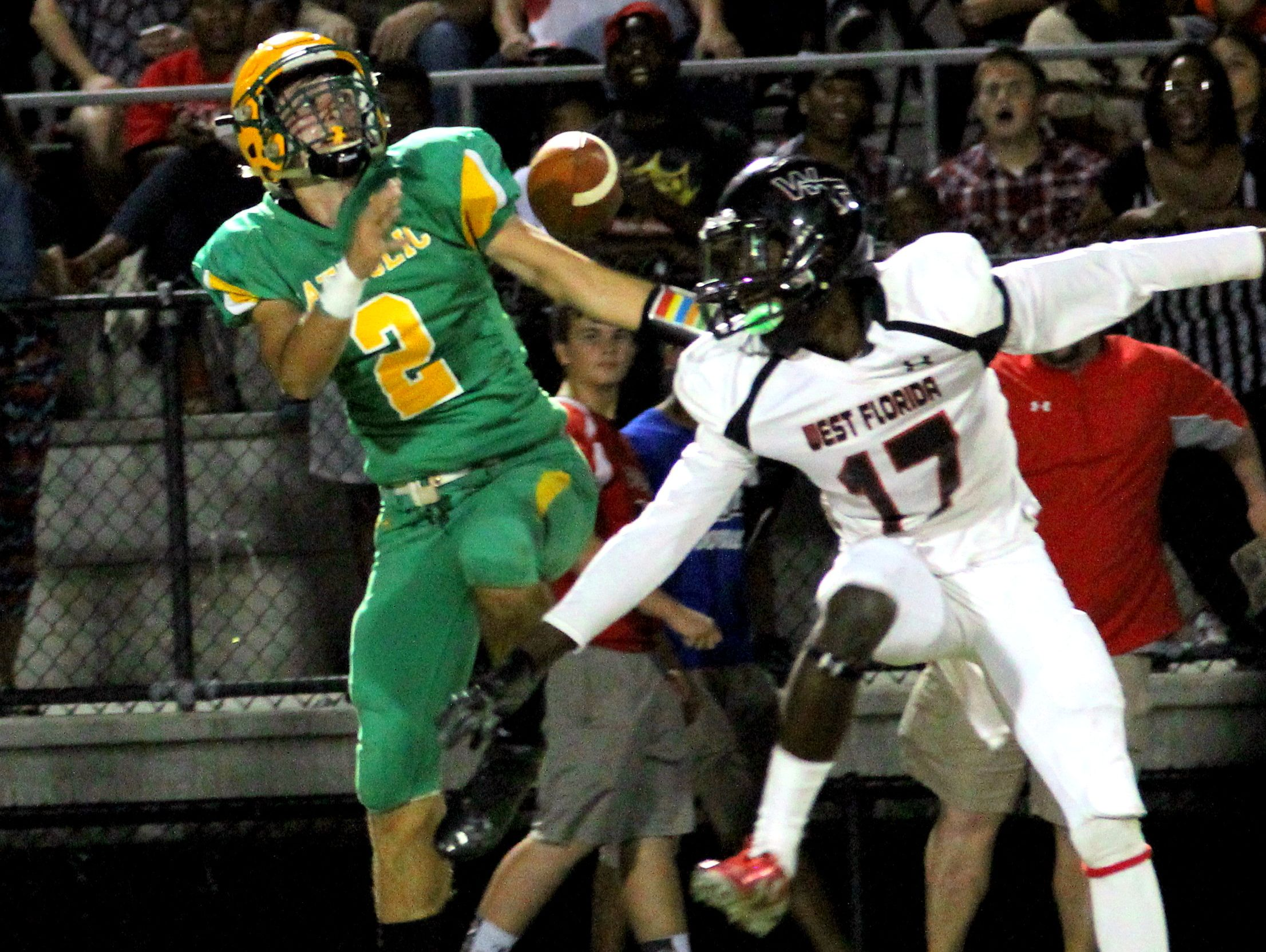 A West Florida player breaks up a pass intended for Catholic's AJ. Yates (2) in the first half.