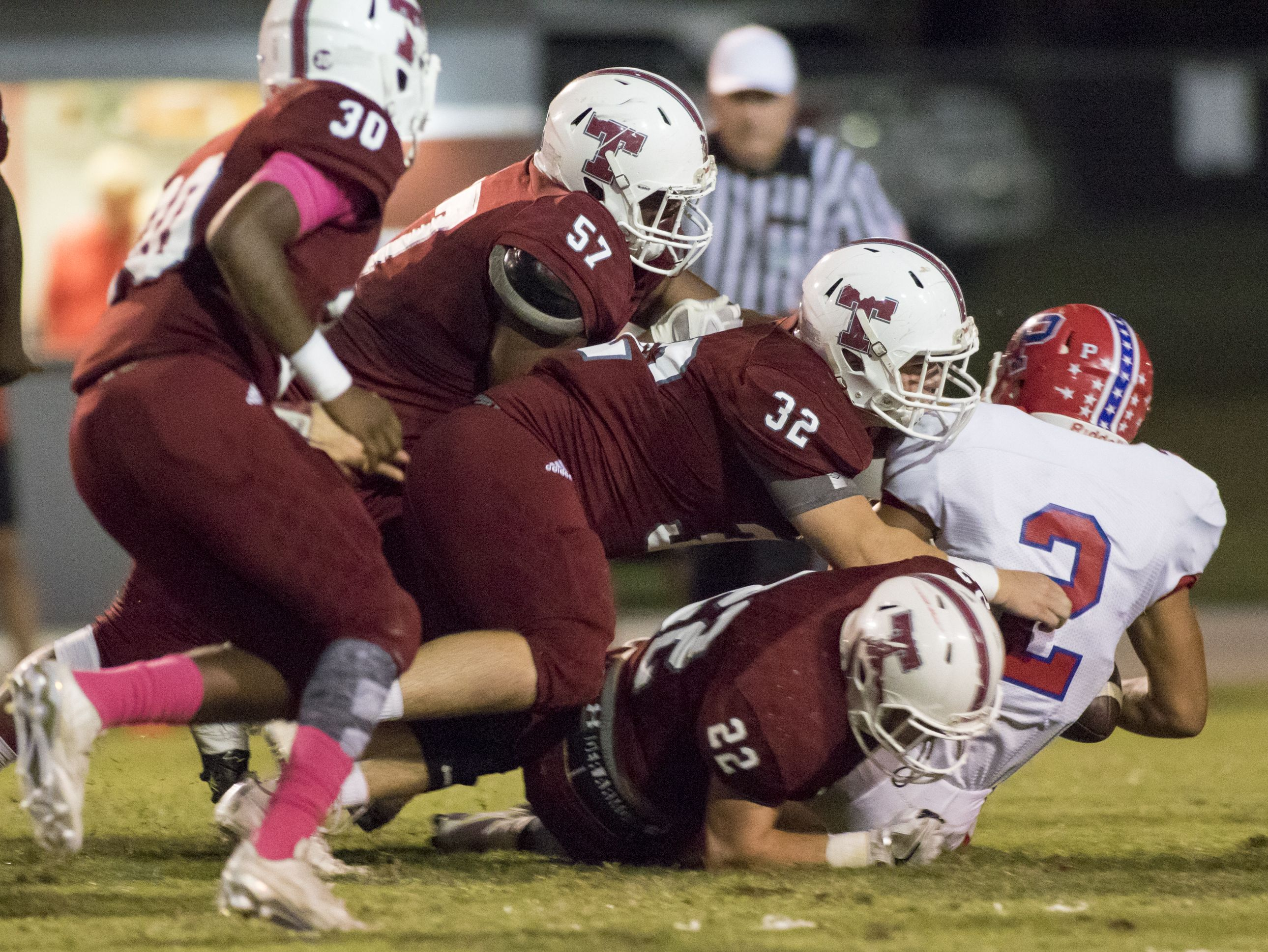 Quarterback Damean Bivins (2) is taken down by the Tate defense during the Pace vs Tate football game at Tate High School on Friday, October 7, 2016.