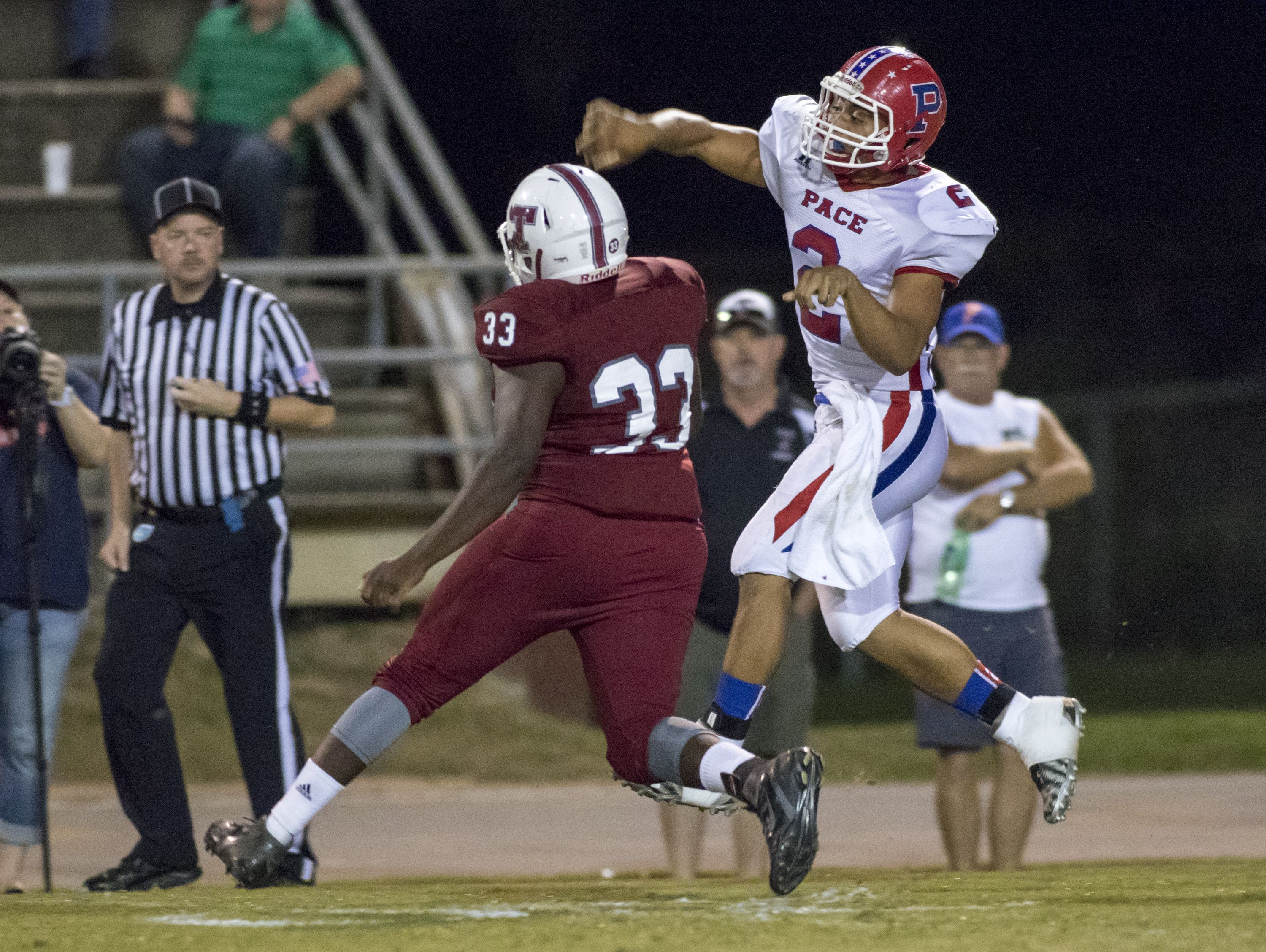 Quarterback Damean Bivins (2) leaps as he gets rid of the ball before Caleb Campell (33) reaches him during the Pace vs Tate football game at Tate High School on Friday, October 7, 2016.