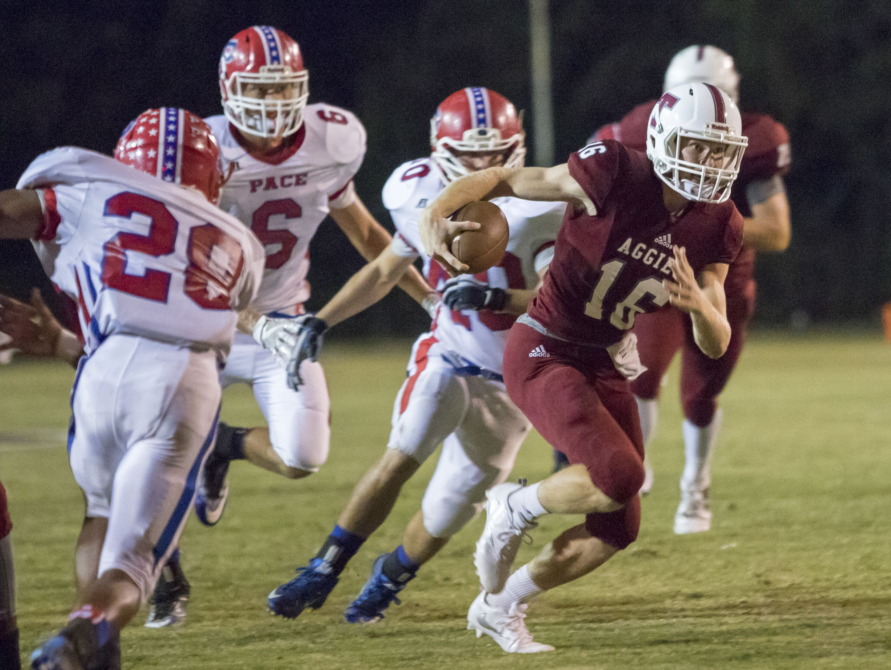 Quarterback Jack Henry (16) keeps the ball during the Pace vs Tate football game at Tate High School on Friday, October 7, 2016.