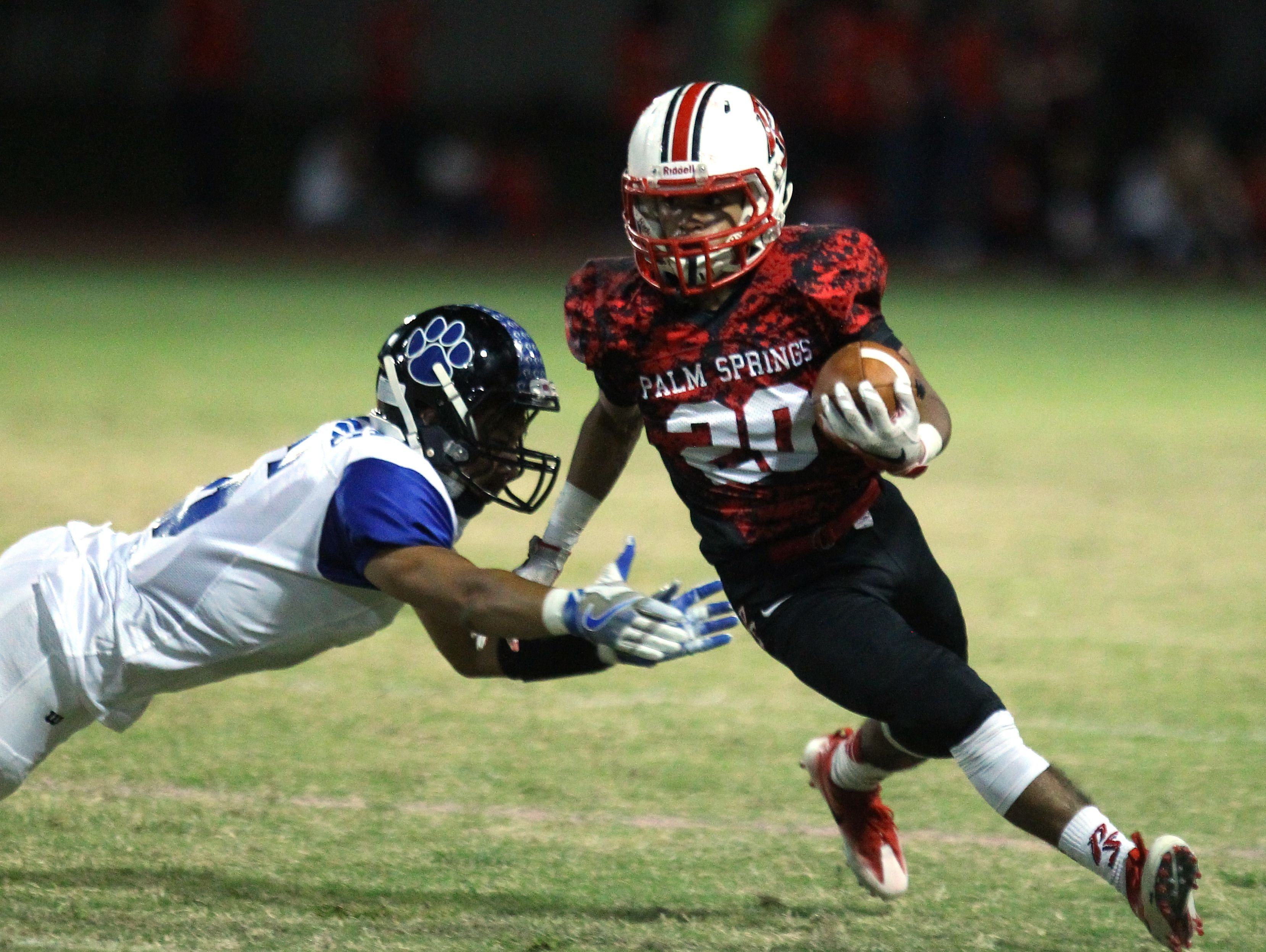 Palm Springs High School's Nick Reyes Foster evades a tackle by Cathedral City High School'during their game at Palm Springs.