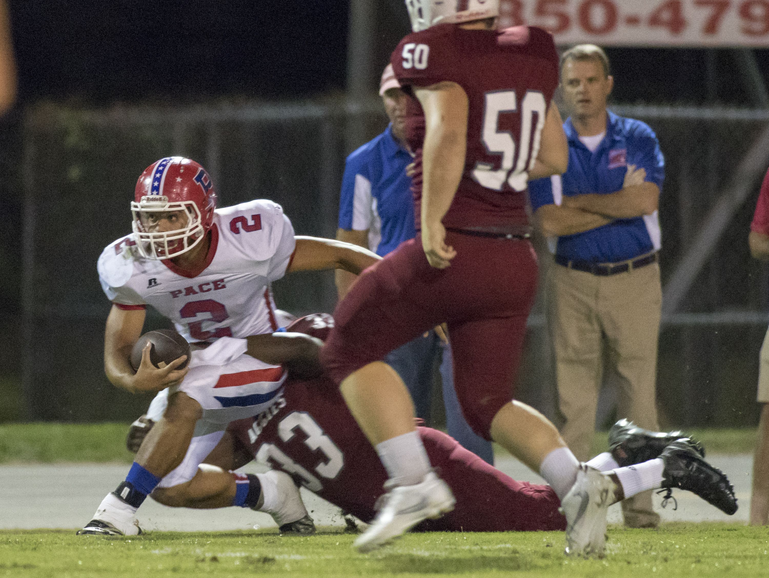 Quarterback Damean Bivins (2) is taken down by Caleb Campell (33) during the Pace vs Tate football game at Tate High School on Friday, October 7, 2016.