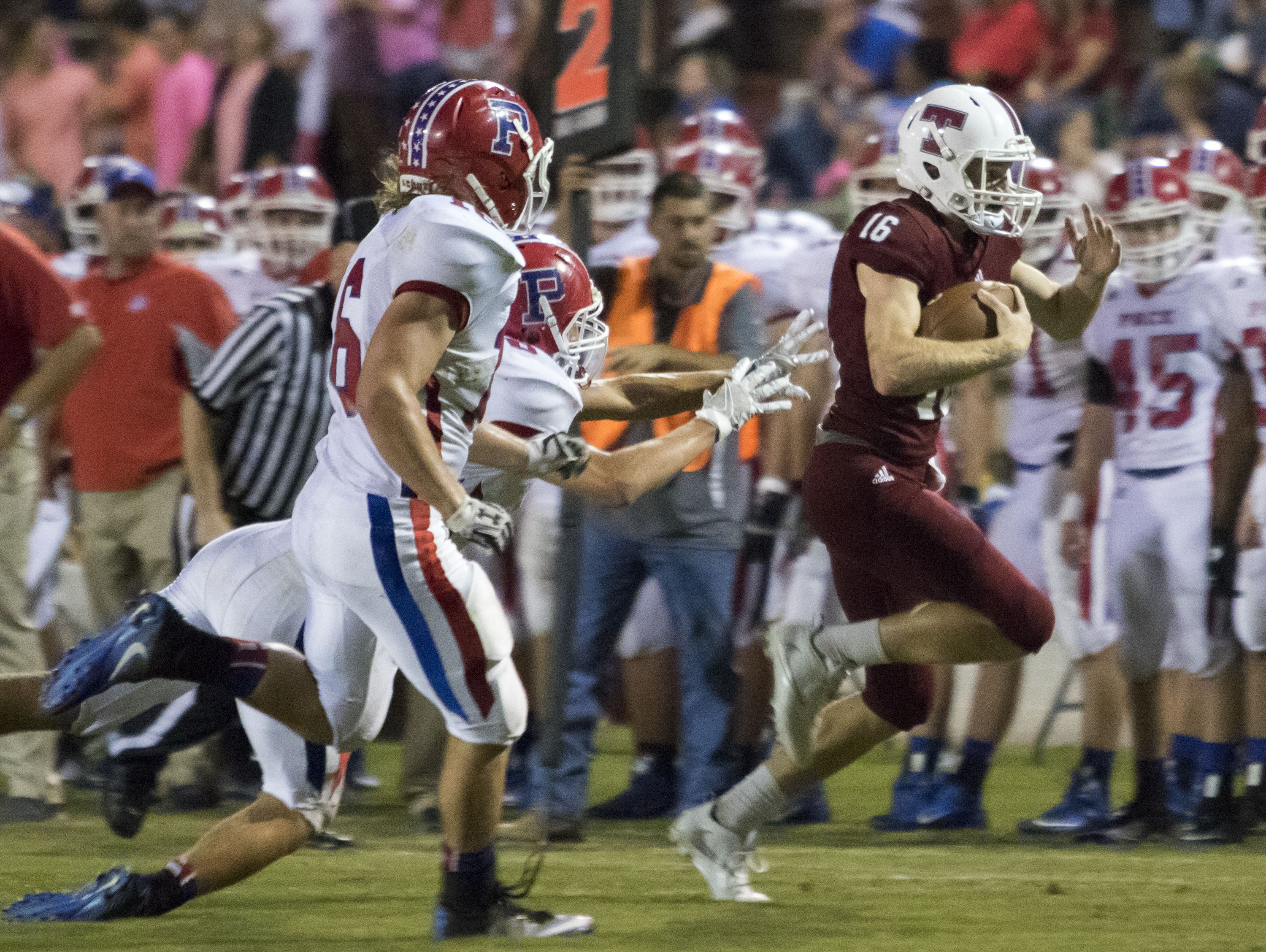 Quarterback Jack Henry (16) escapes the Pace defense for a big run during the Pace vs Tate football game at Tate High School on Friday, October 7, 2016.